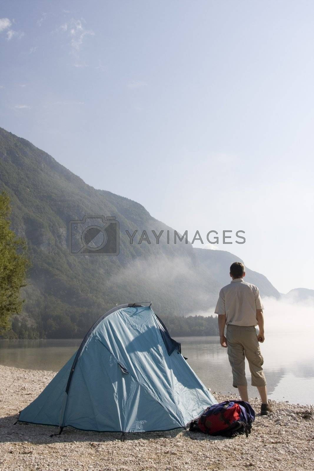 Man standing beside his tent at mountain lake
