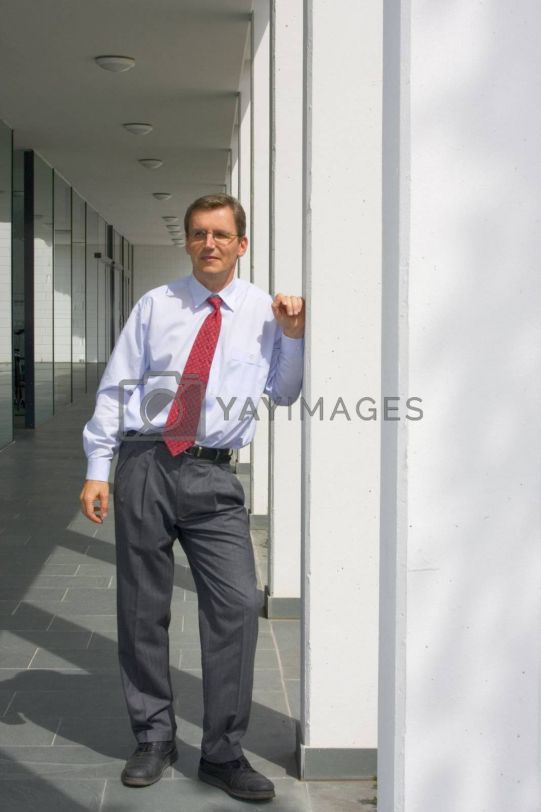 Serious looking business man leaning at a column of an office building