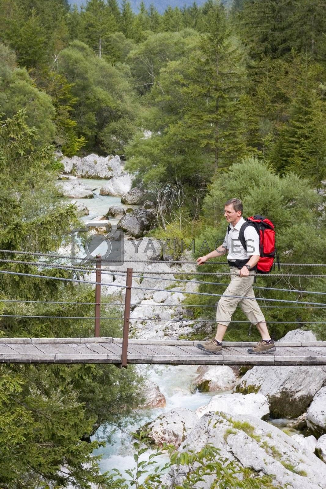 Hiker with rucksack crossing a rope bridge in the wilderness