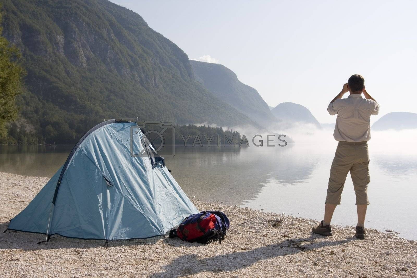 Man standing beside his tent at mountain lake and looking through field glasses
