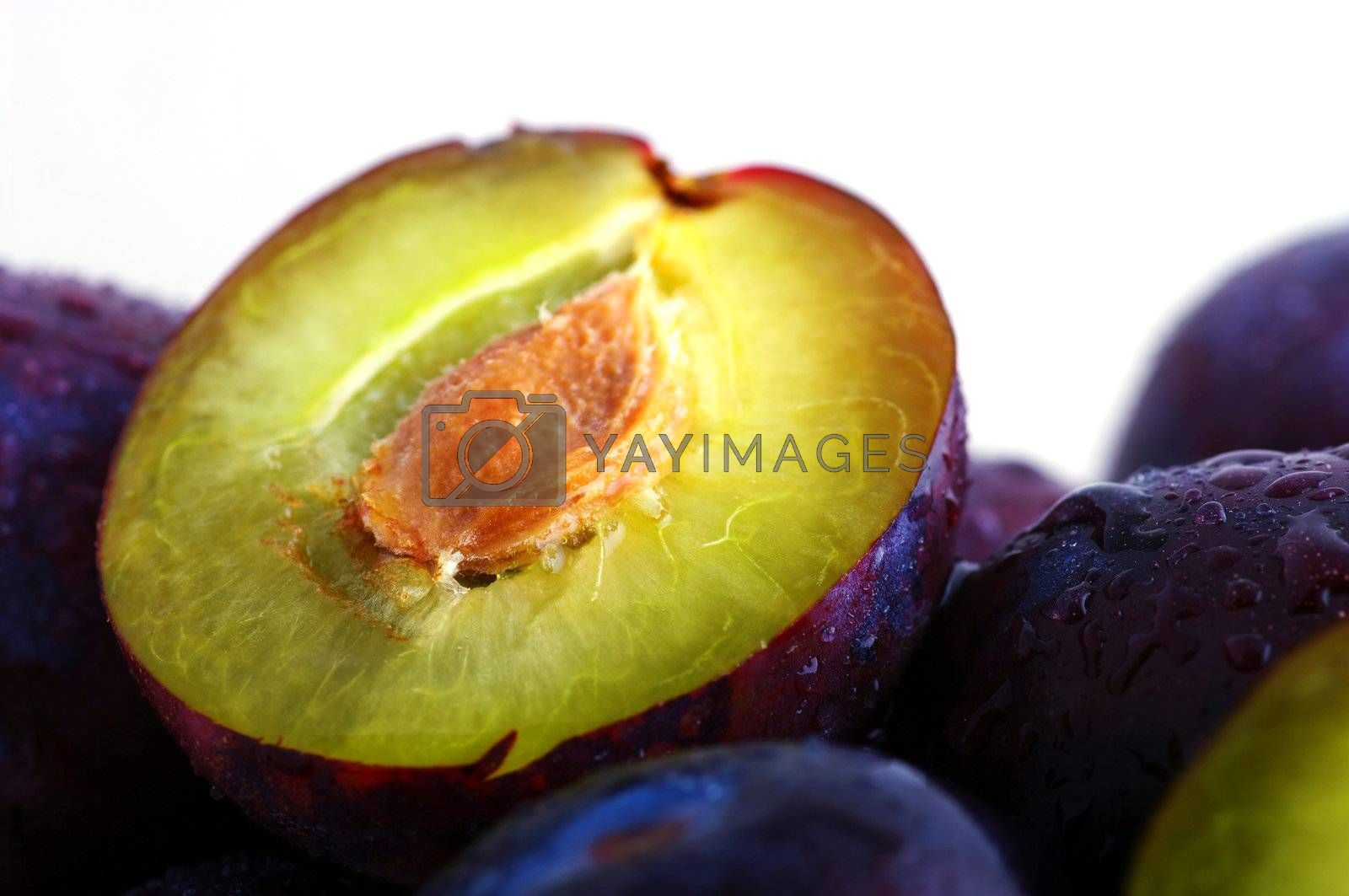 Royalty free image of Half of plums isolated on white background by dolnikow