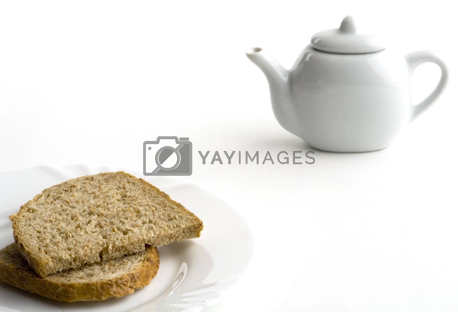 Closeup of bred on white plate and tea pot. White background. Selective focus.