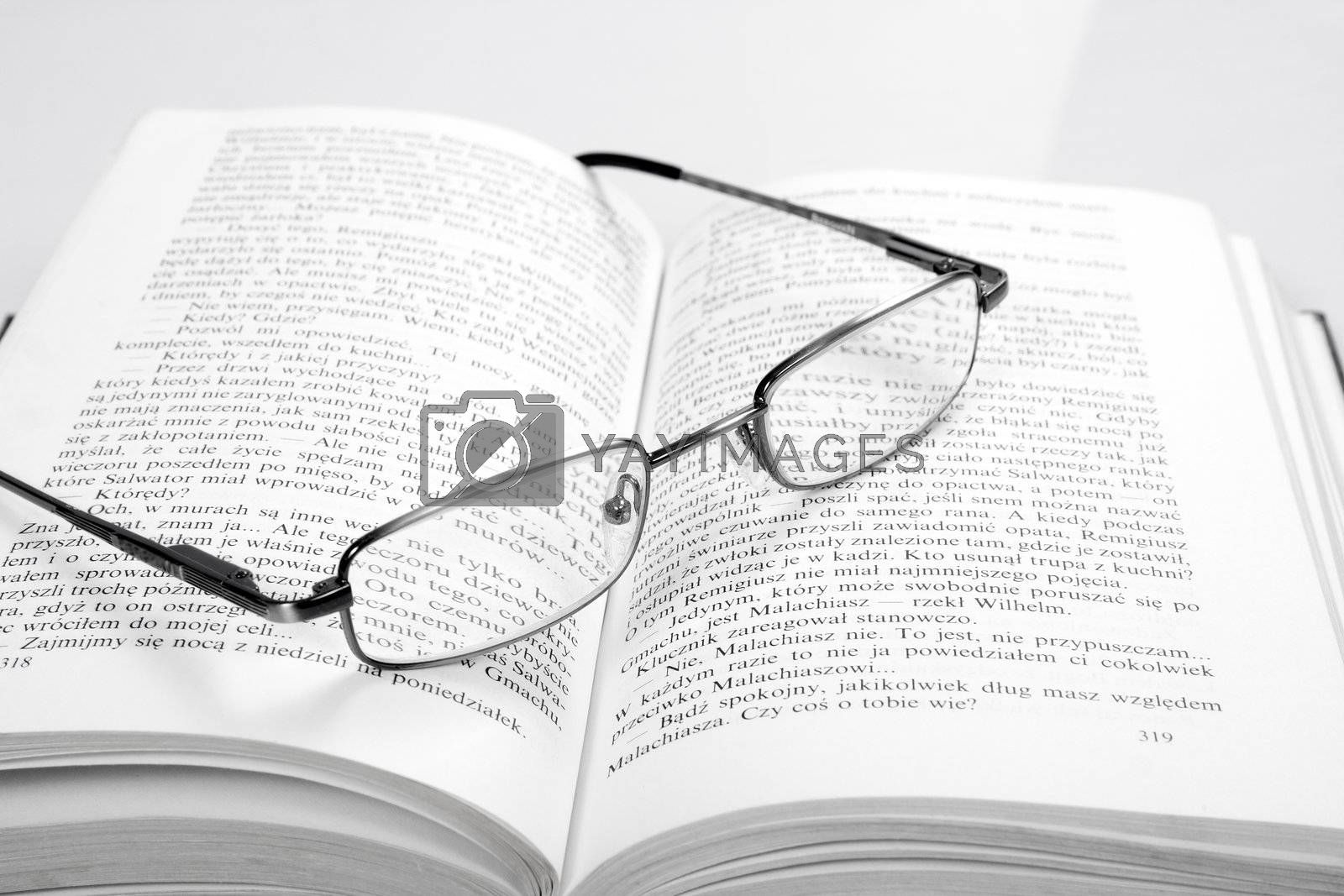 the reading glasses on a open book