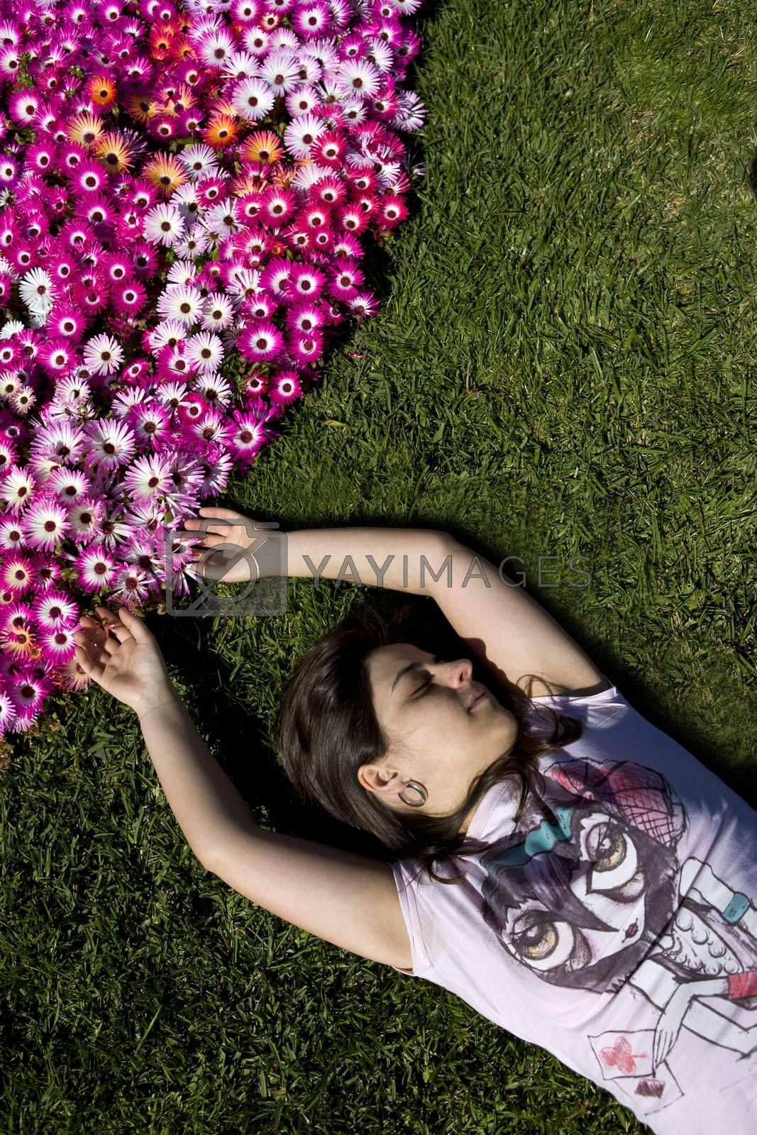 beautiful young woman in the grass with colorful flower bouquet