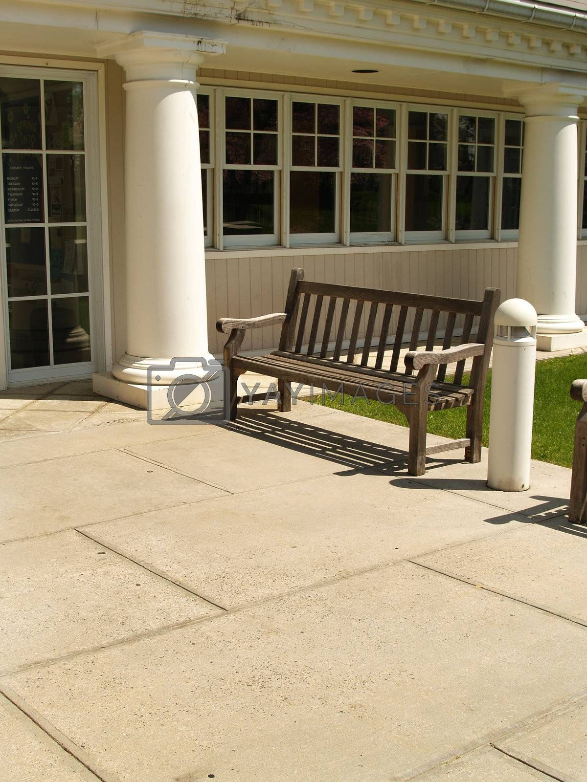 an empty bench outside a building by a sidewalk on a sunny day