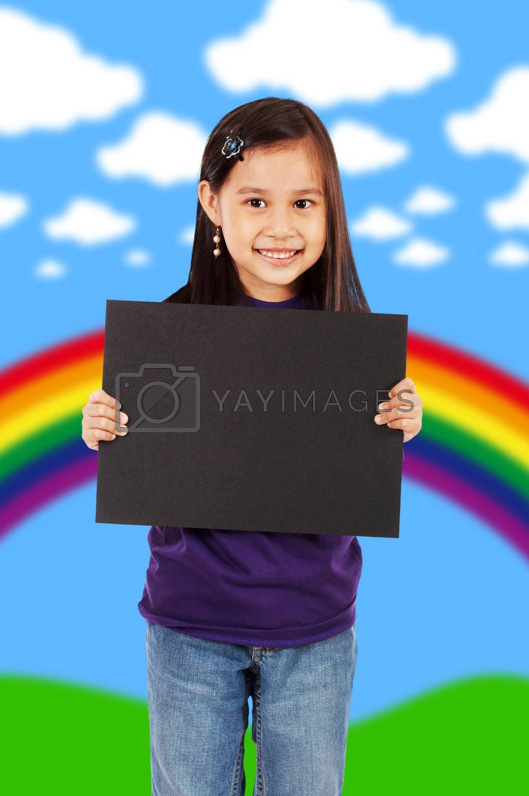A Smiling Girl Holding A Blank Black Board With An Abstract Rainbow And Clouds Background