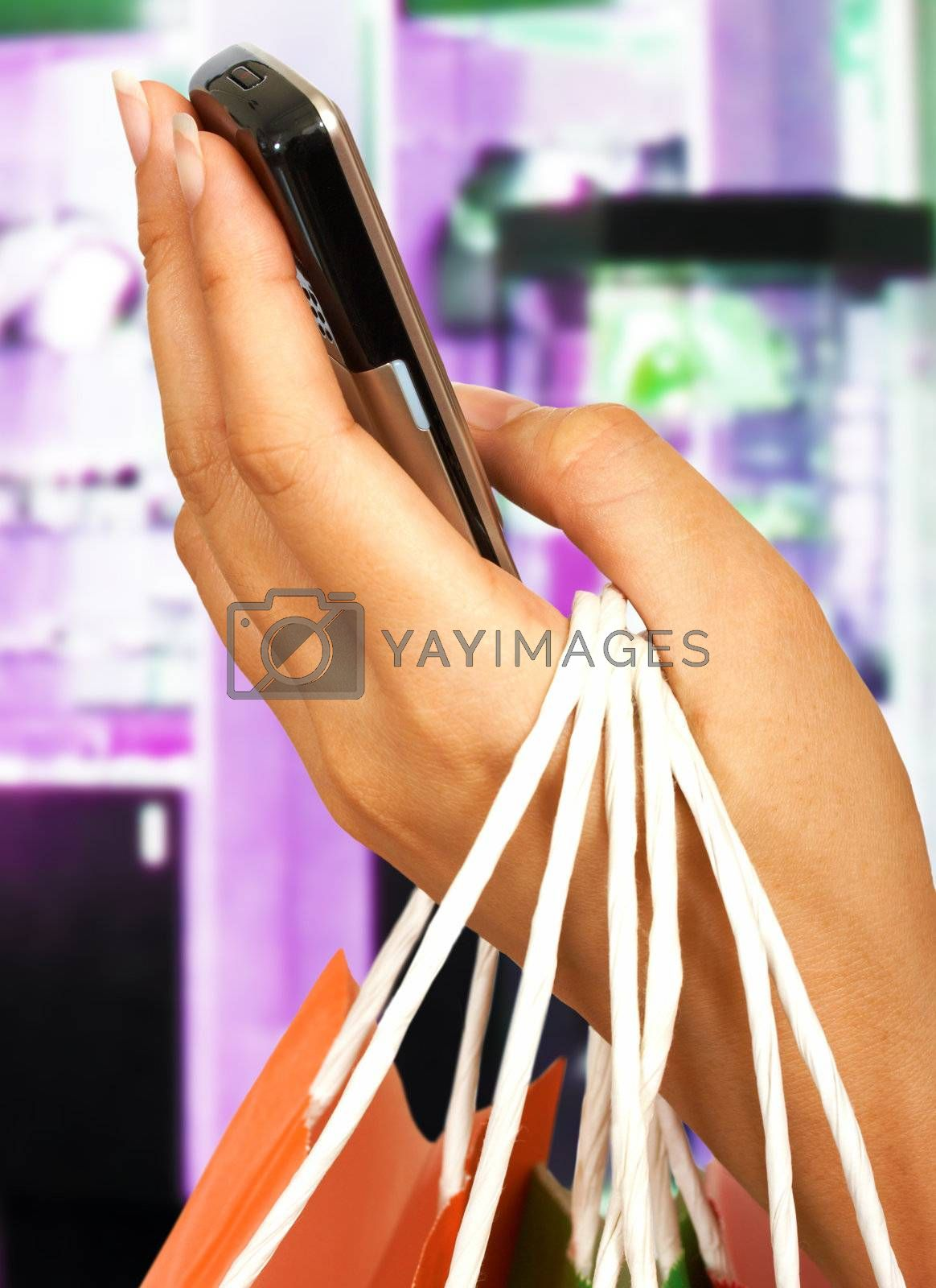 Holding A Mobile Phone And Shopping Bags In Front Of A Jewelry Store