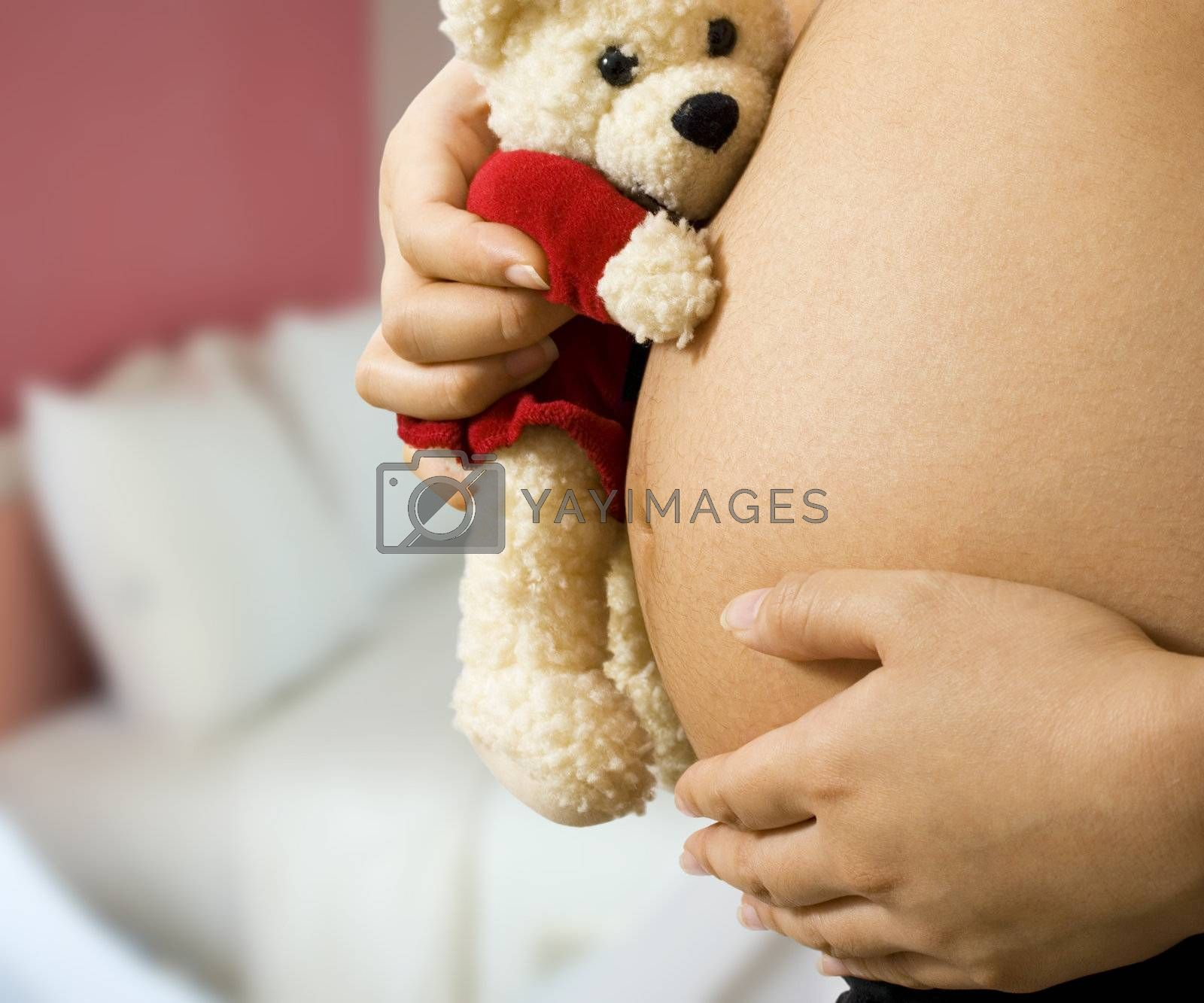 Mom in pregnancy holding a teddy bear in her bedroom