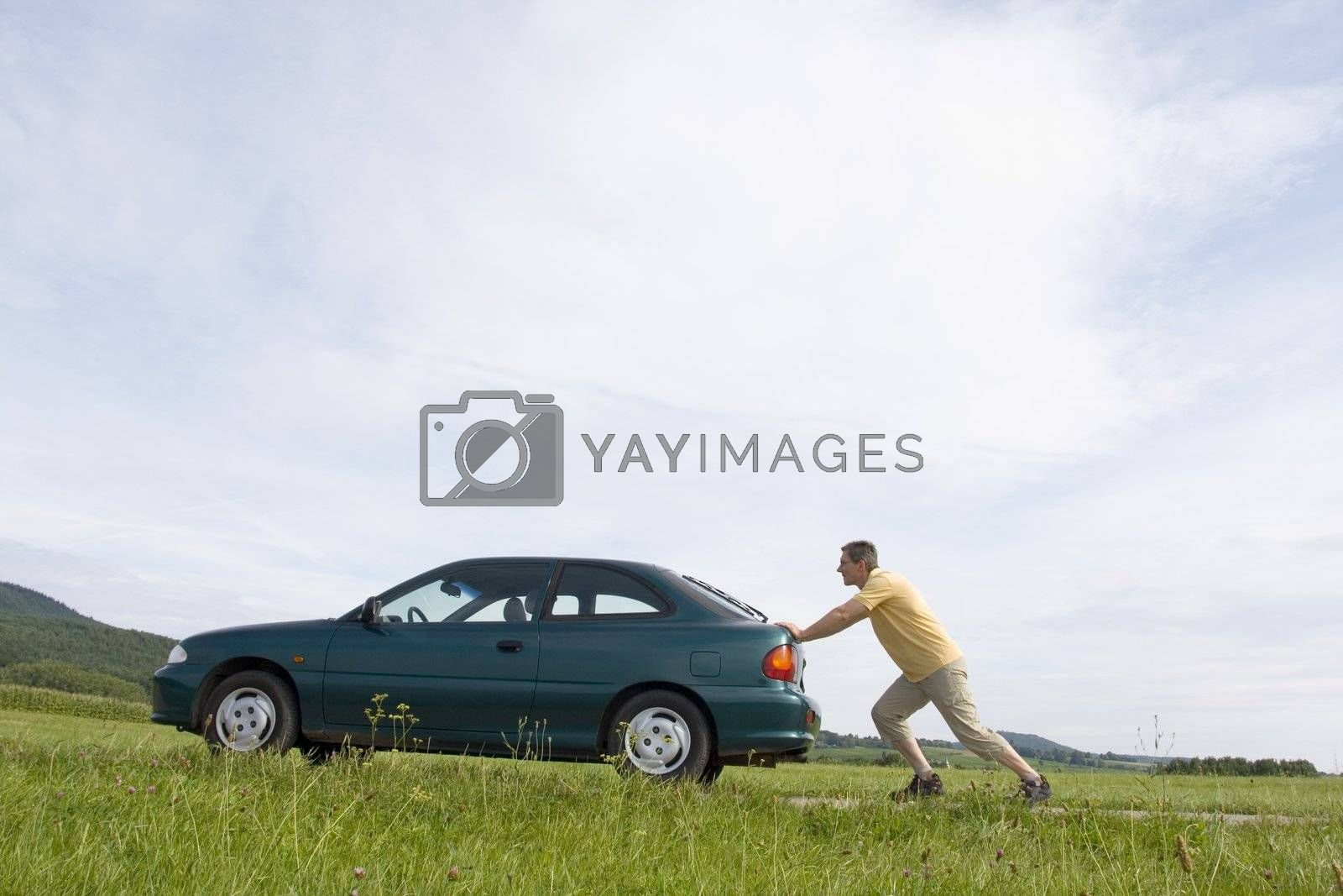Man pushing his automobile with empty fuel tank
