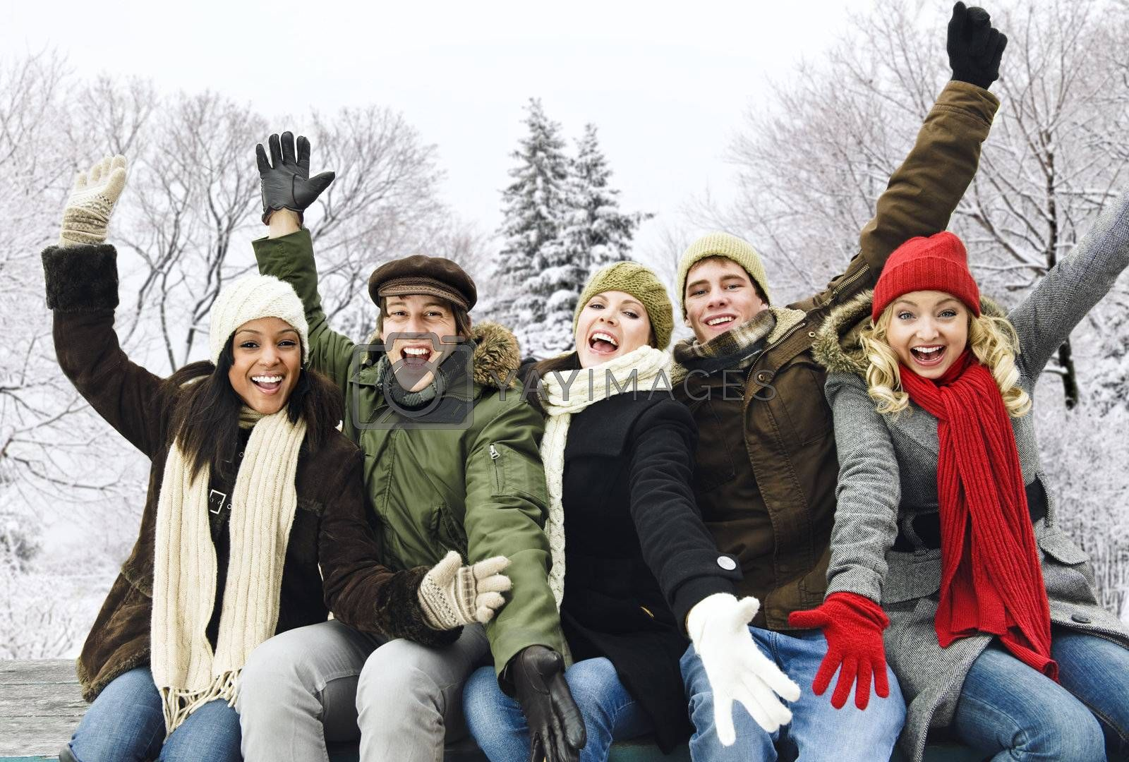 Group of excited young friends with arms raised outdoors in winter