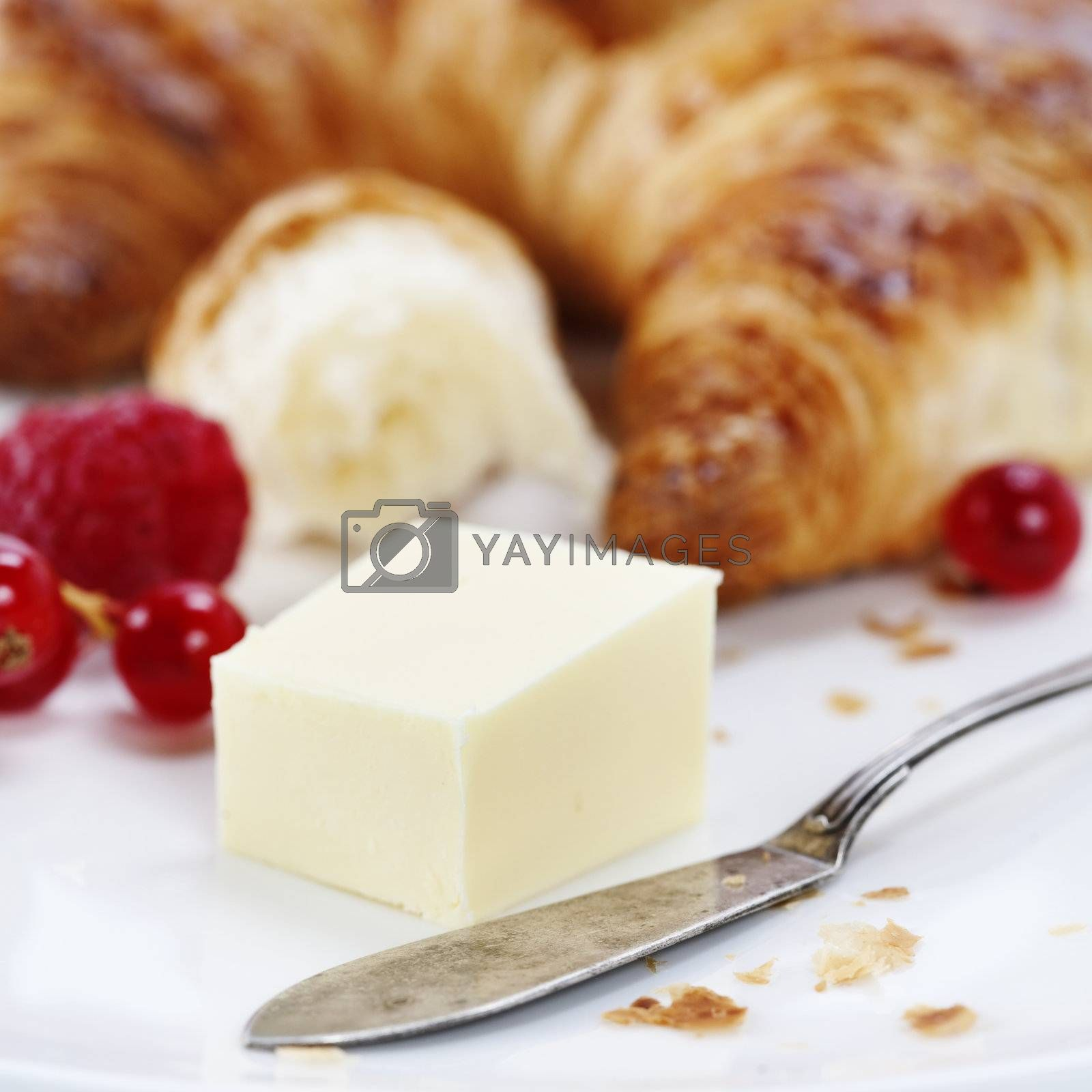 fresh croissant with butter, berry and knife