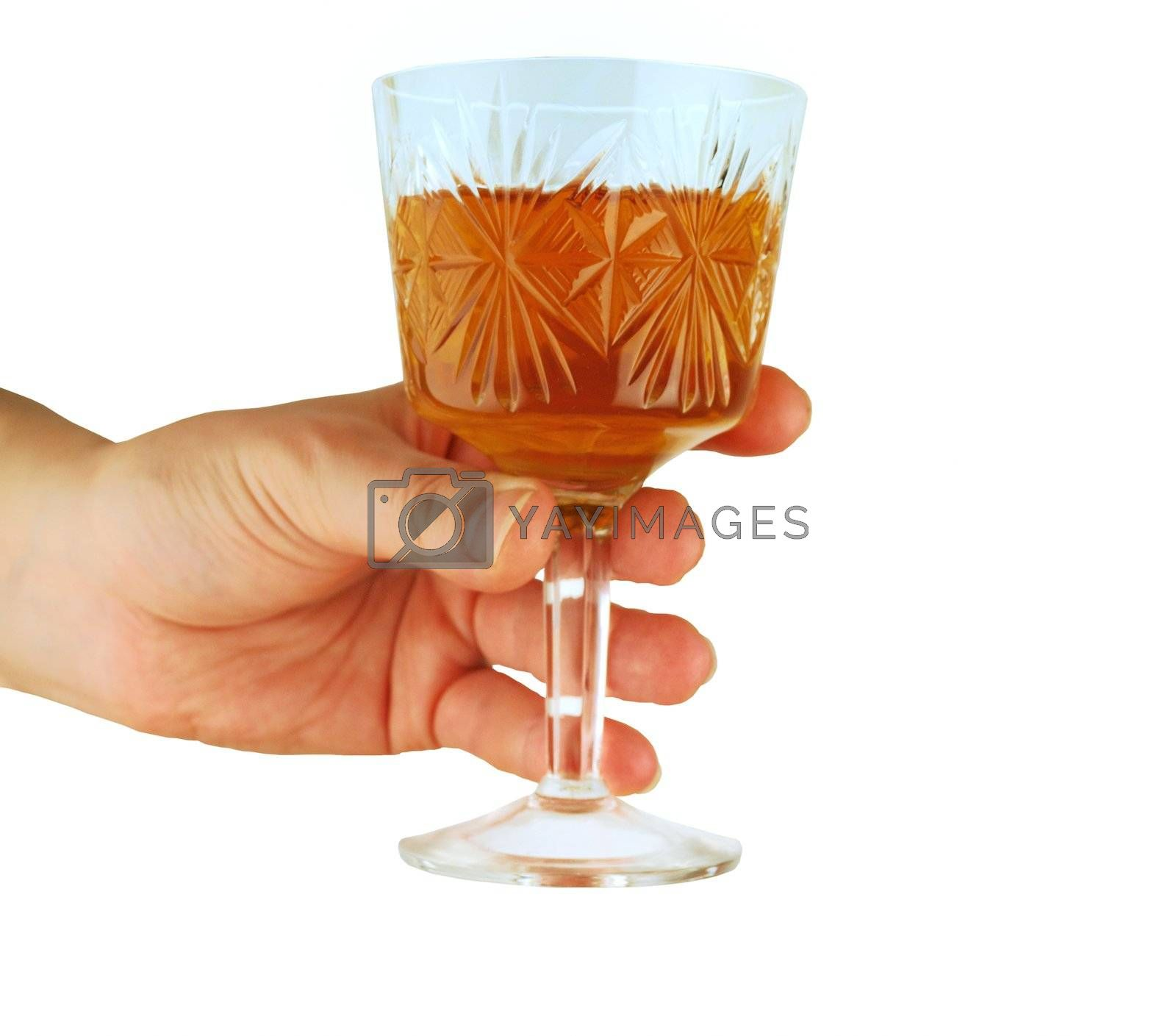 a womanish hand holds a crystal glass with wine