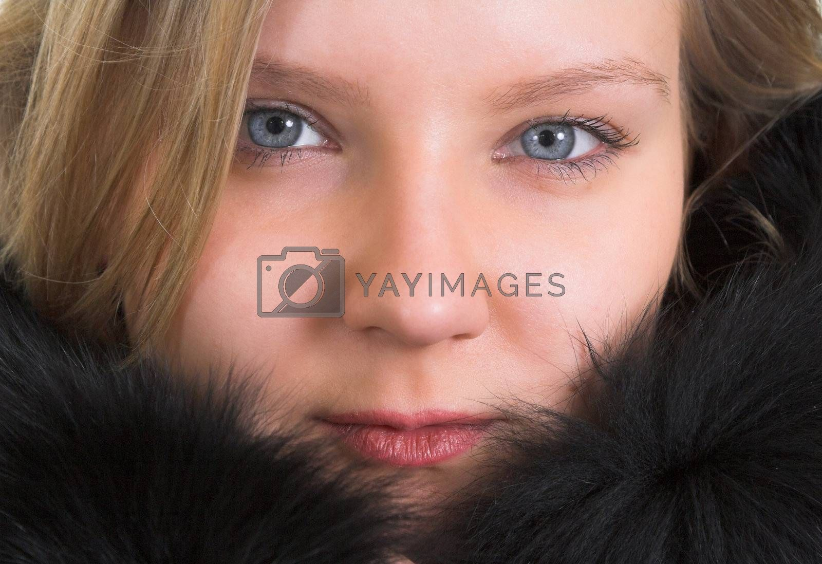 Head portrait of a pretty young lady in a black fur coat