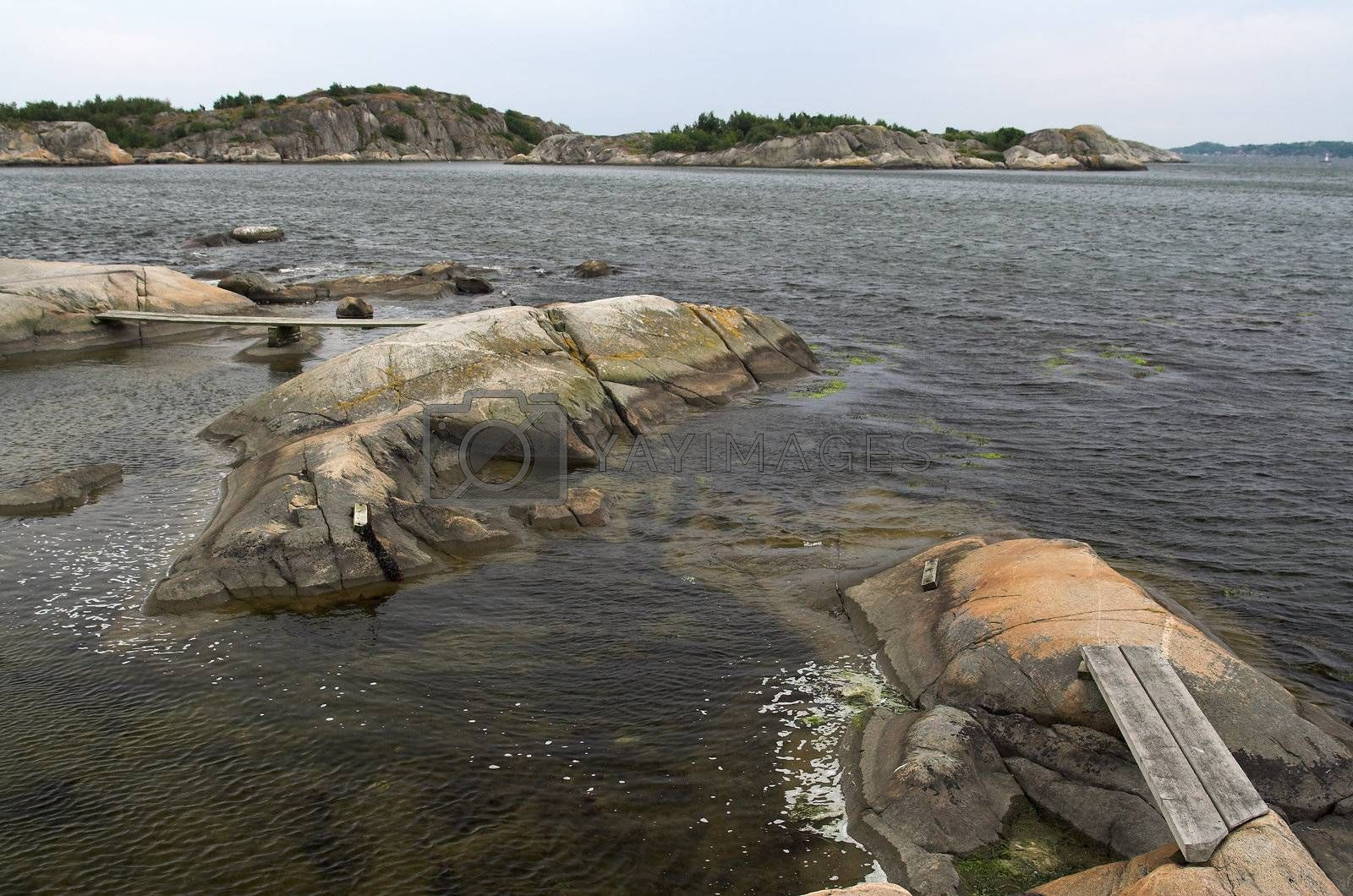 Rocks in the sea, connected by a wooden foot path; a rocky island in the background. Western Swedish coast.