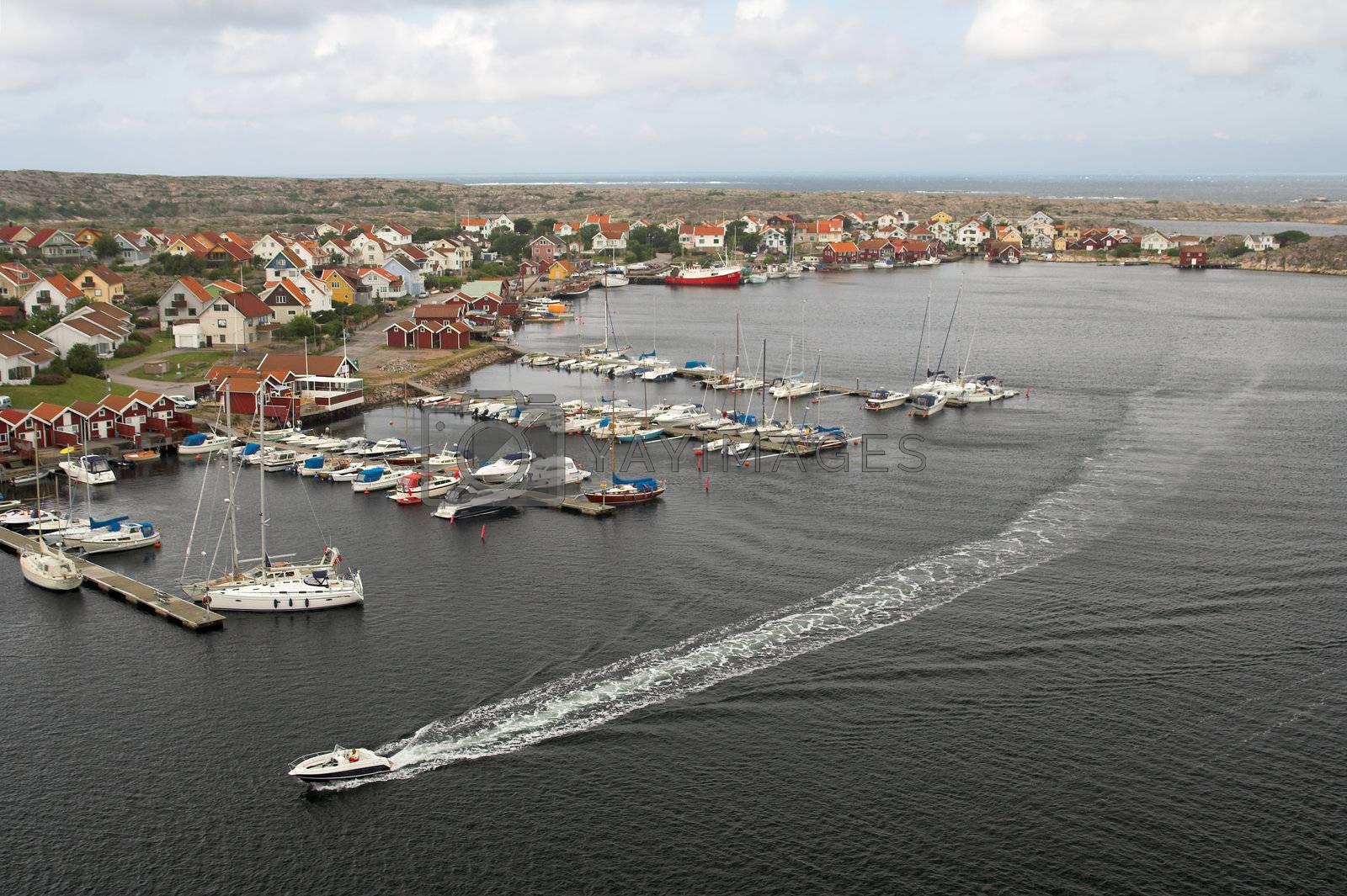 Yacht passing along the marina of a Swedish fishermen village.