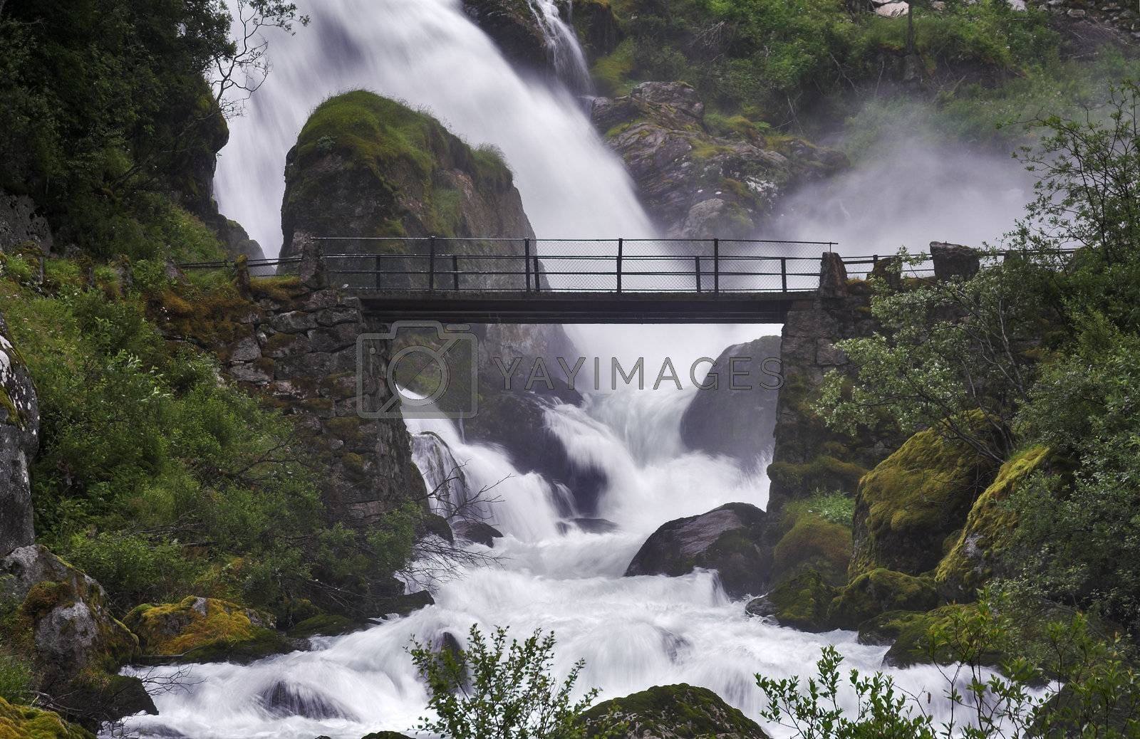 Bridge across the stream near a powerful waterfall surrounded by misty clouds