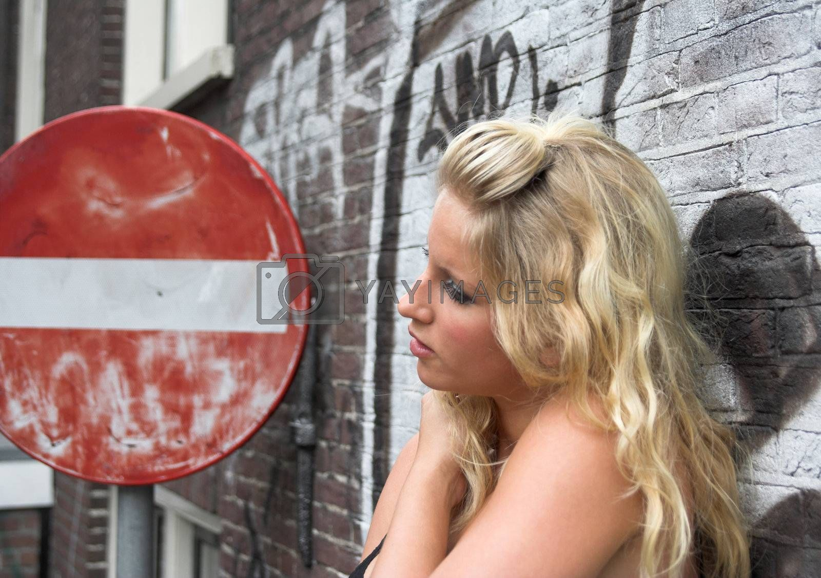 Attractive blonde against a brick wall with graffiti, standing next to a red road sign