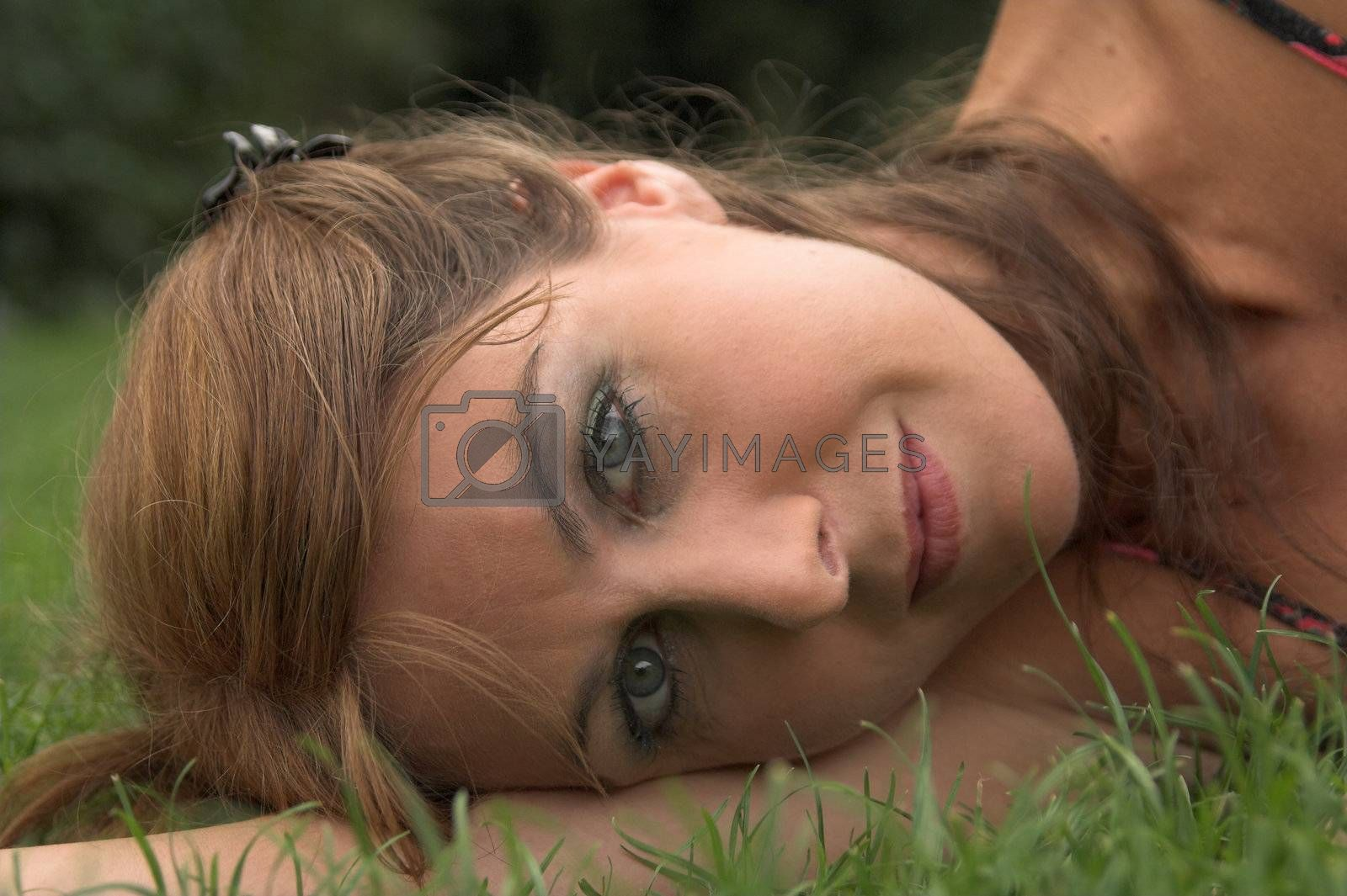 Head portrait of a pretty woman laying on the grass