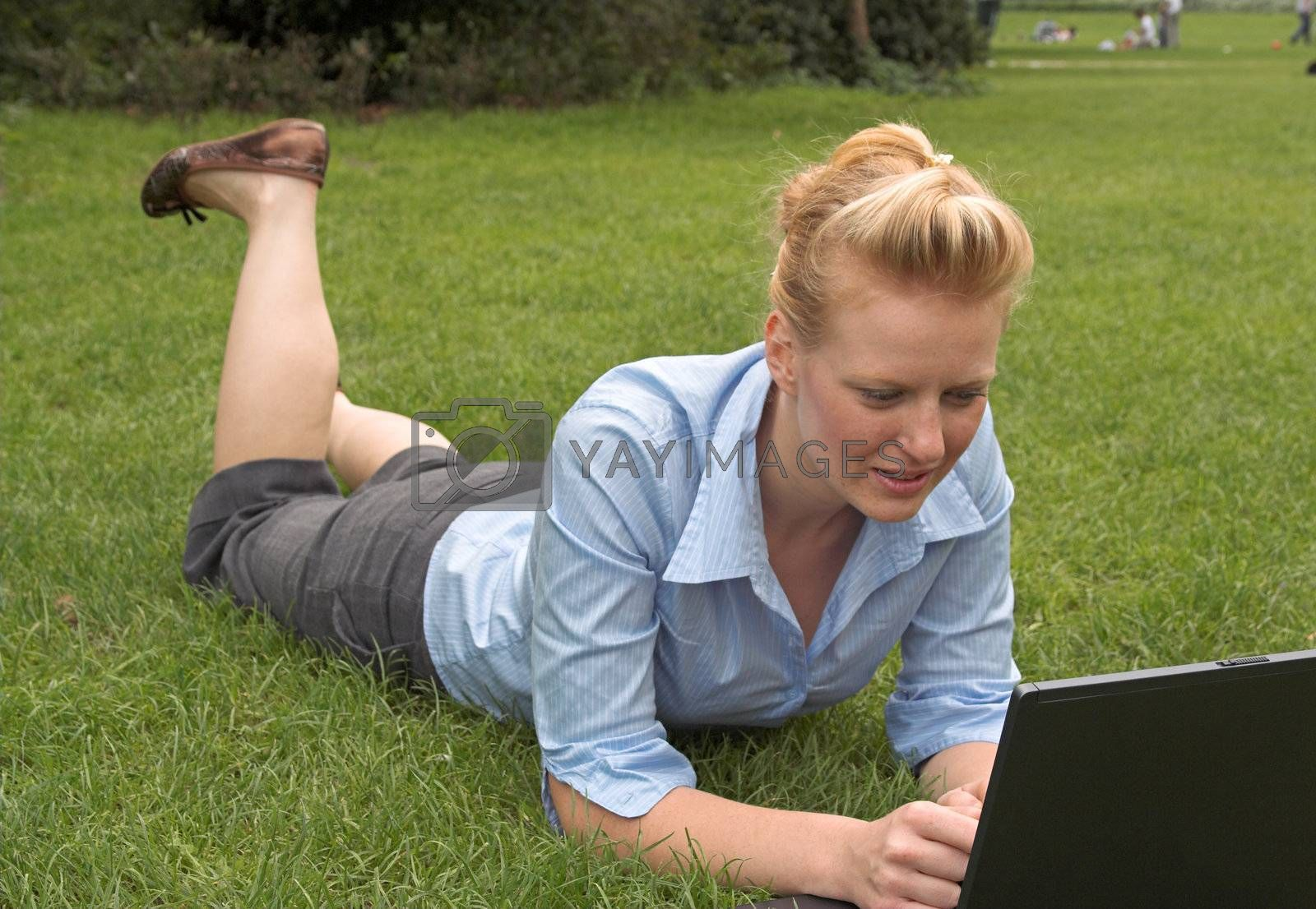 woman laying on the grass, working with laptop