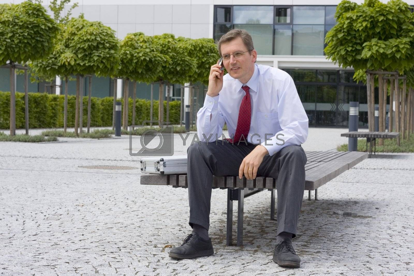 Businessman talking on mobile phone while sitting on a bench in front of an office building
