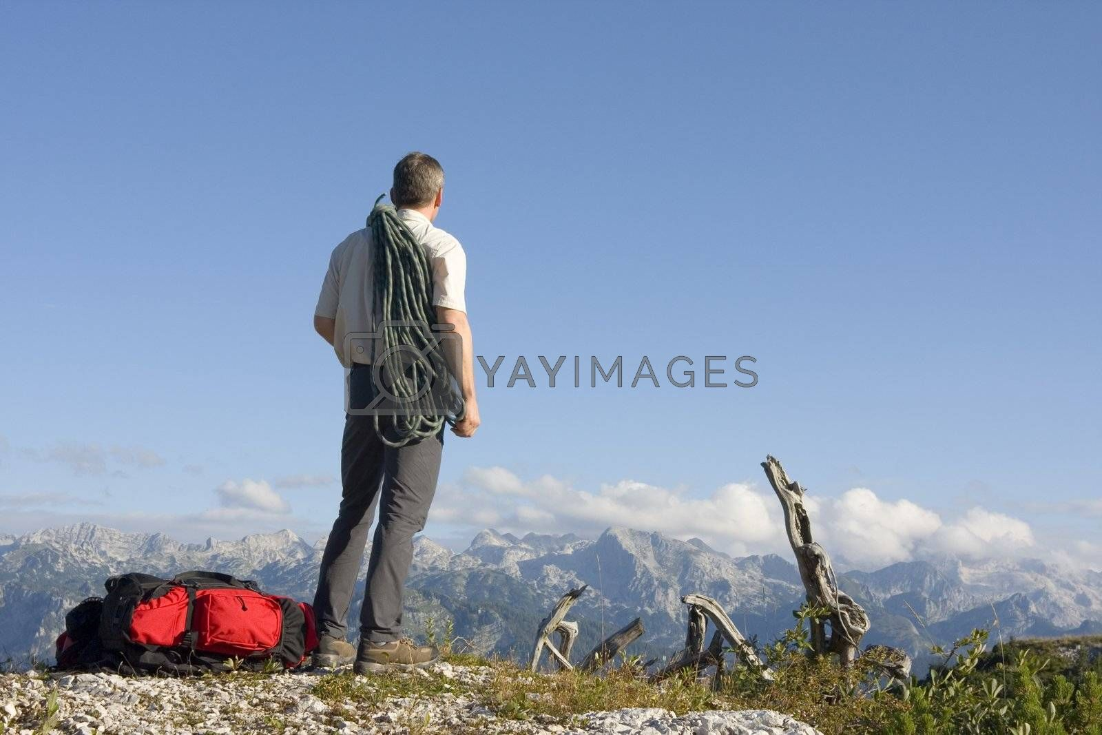 Mountaineer with rope on mountain peak contemplating the landscape