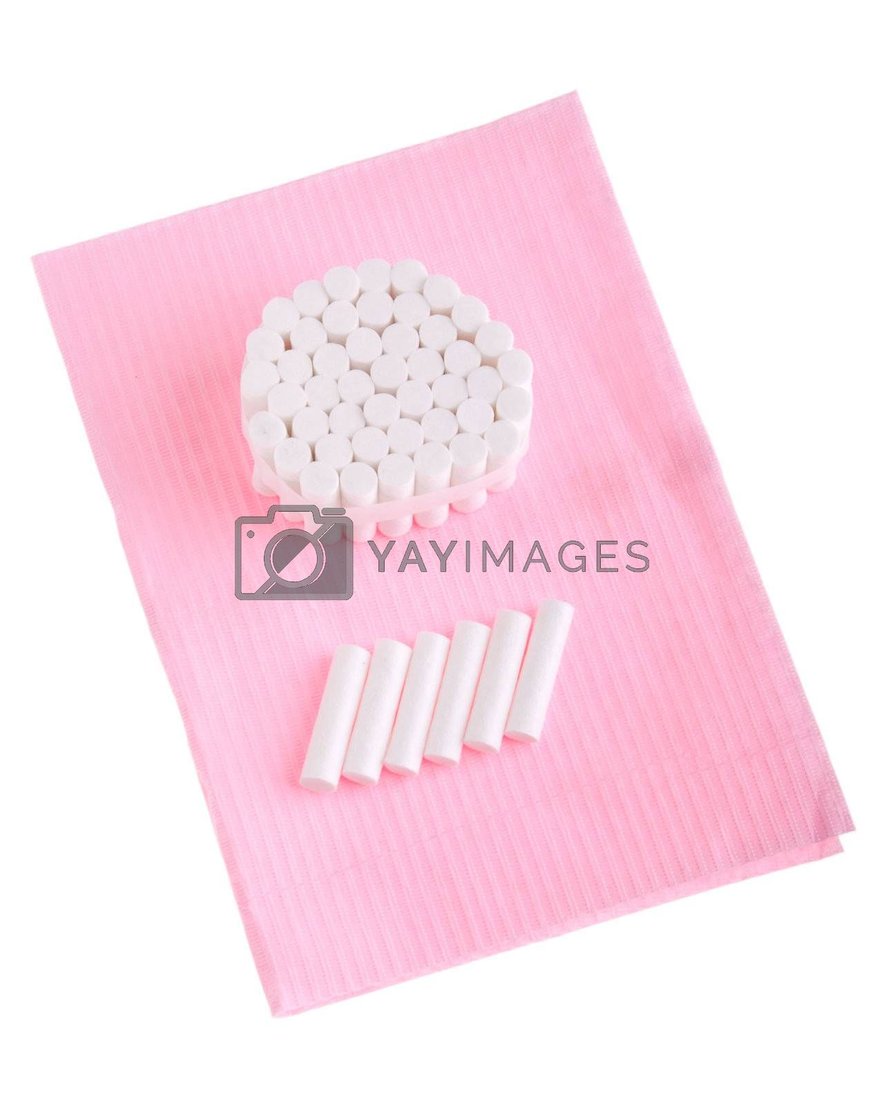 dental cotton rolls on a pink bib (isolated on white background)