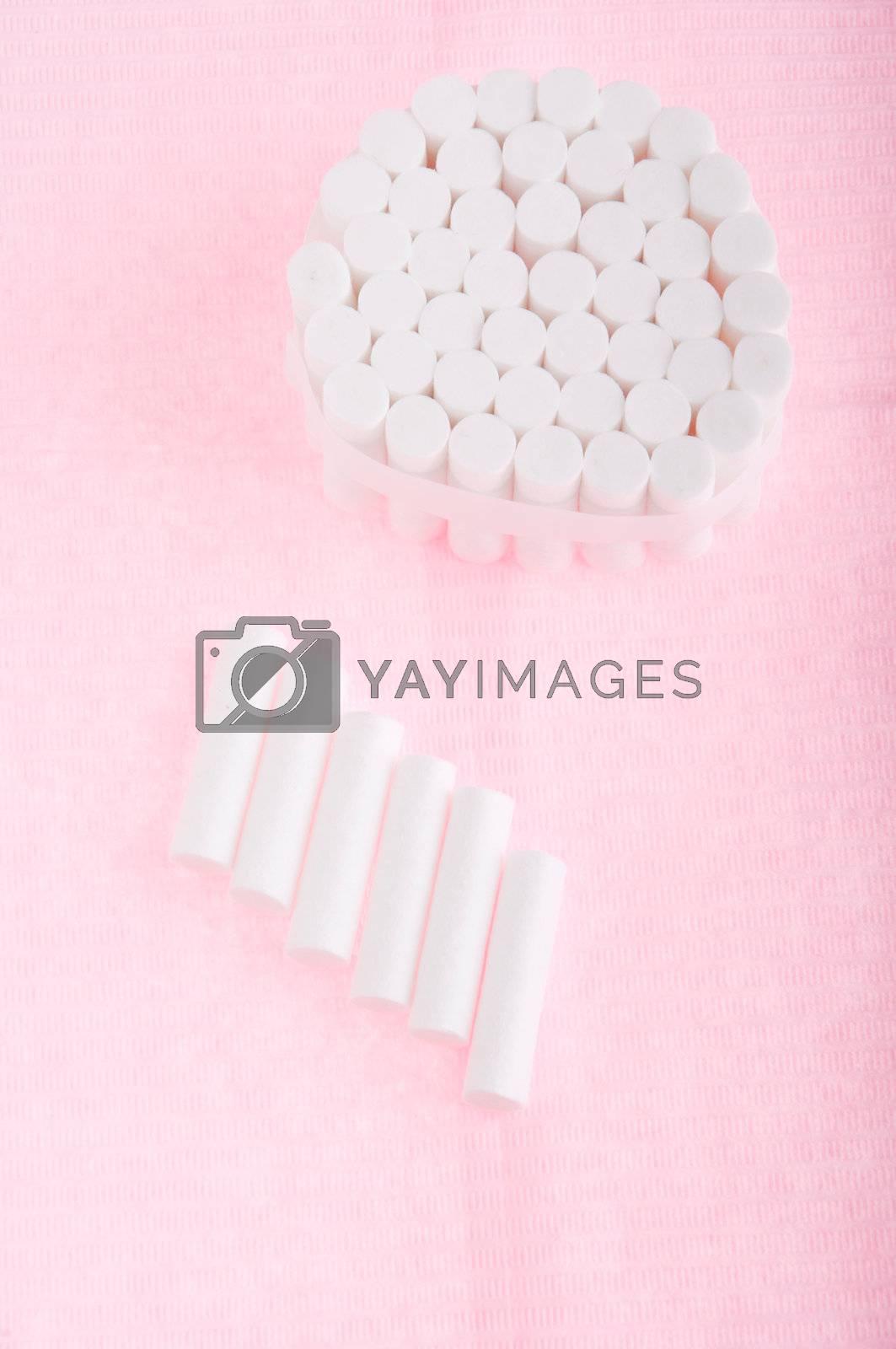 dental cotton rolls on a pink bib (dentistry equipment)