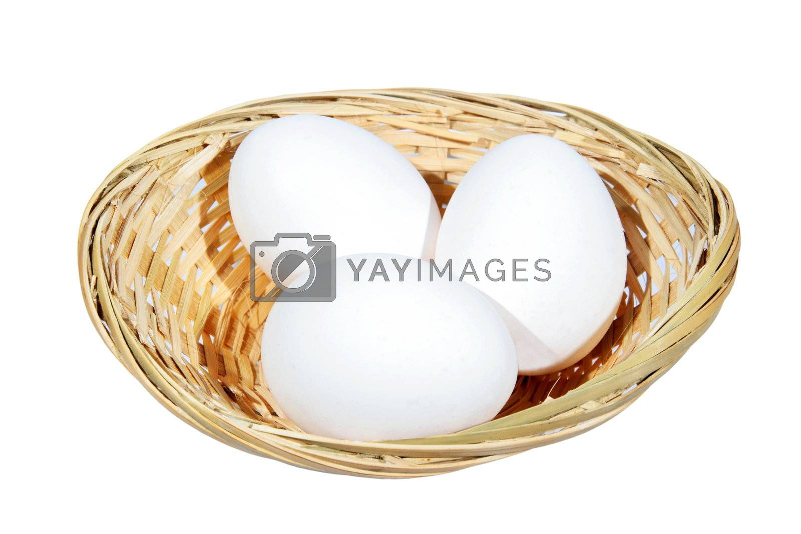 Chicken eggs in a wicker basket on the white background
