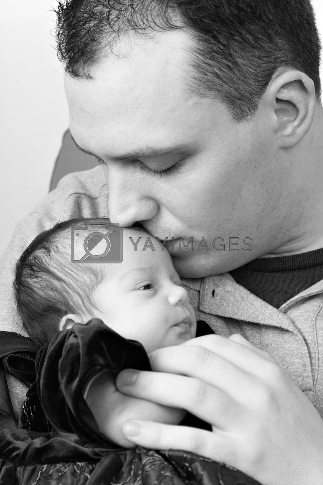 A newborn baby girl being by her dad as he kisses her head in black and white.