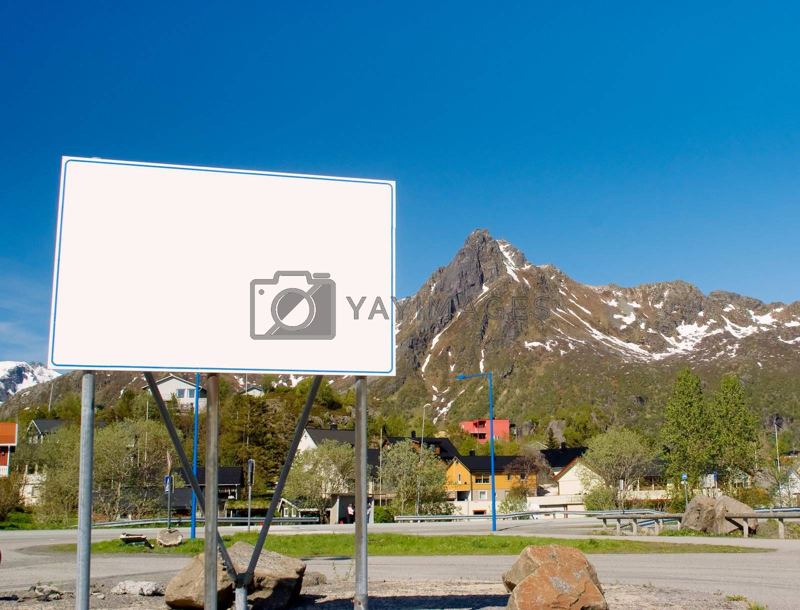 Big white billboard in the background of rocky mountains