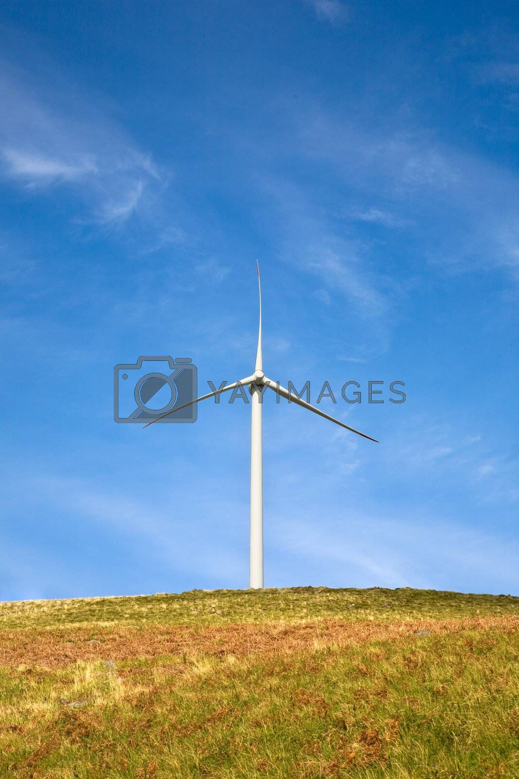 Wind tower on a field with blue sky.