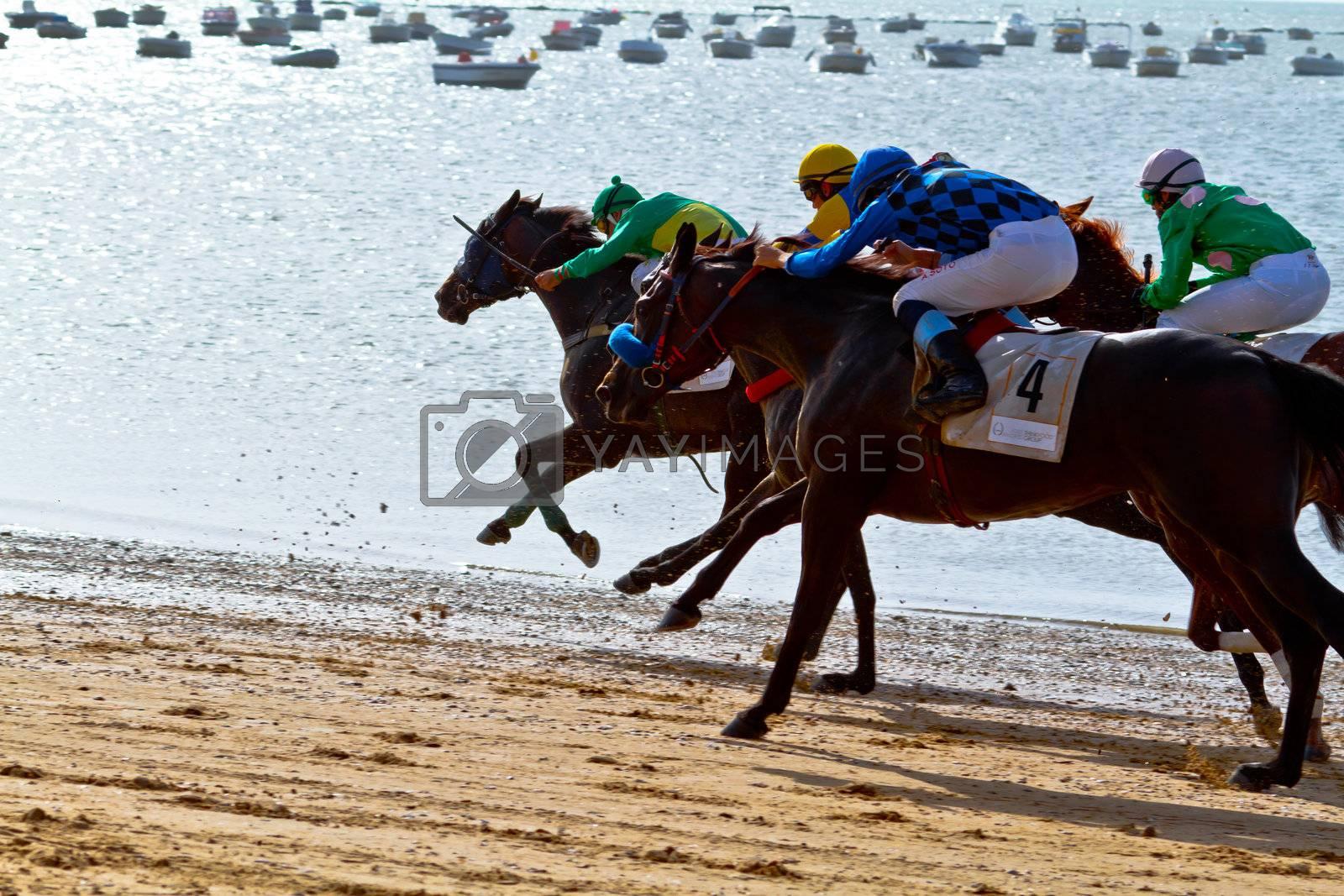 SANLUCAR DE BARRAMEDA, CADIZ, SPAIN - AUGUST 10: Unidentified riders at the start of race horses on Sanlucar de Barrameda beach on August 10, 2011 in Sanlucar de Barrameda, Cadiz, Spain.