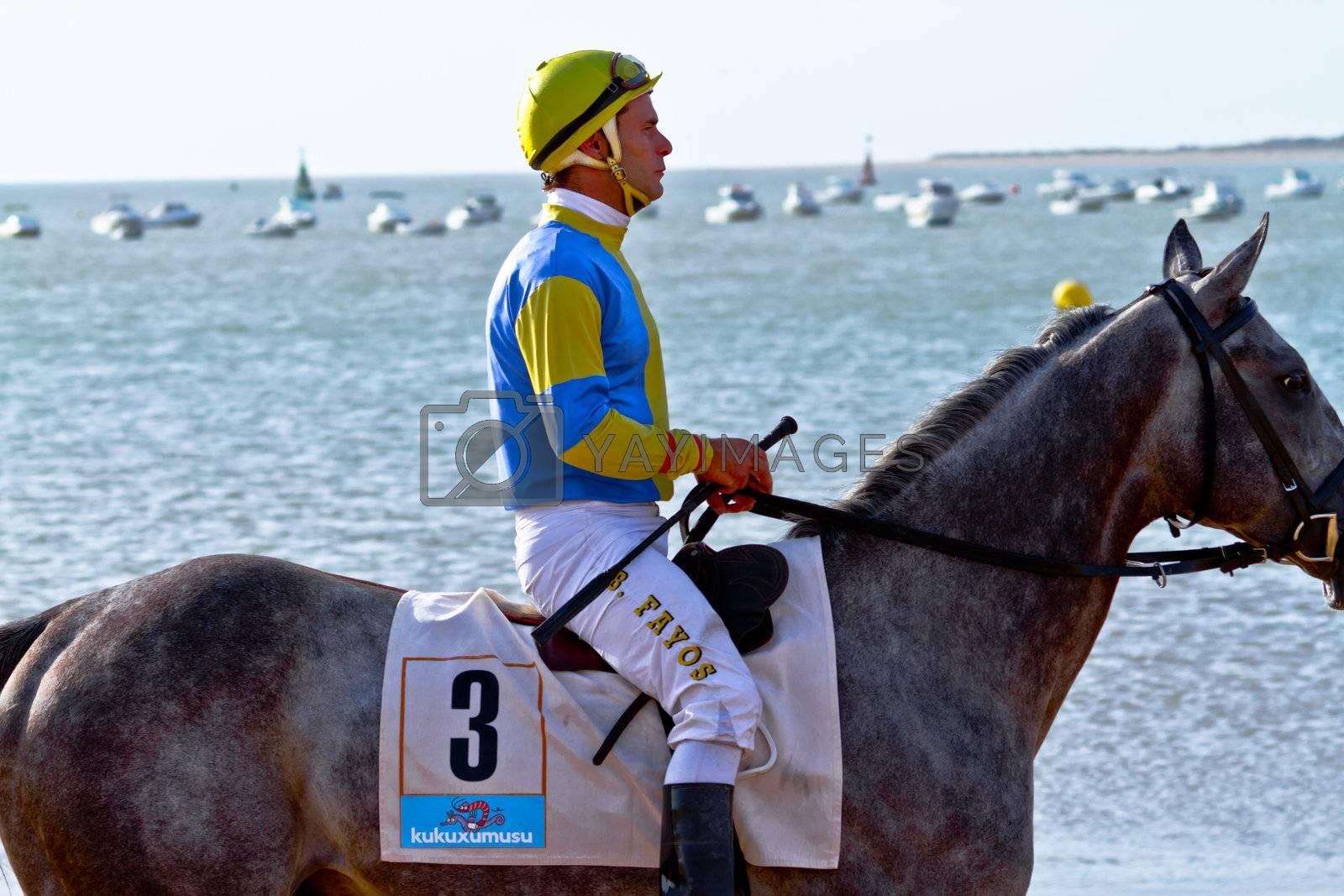 SANLUCAR DE BARRAMEDA, CADIZ, SPAIN - AUGUST 10: Unidentified rider at the start of race horses on Sanlucar de Barrameda beach on August 10, 2011 in Sanlucar de Barrameda, Cadiz, Spain.