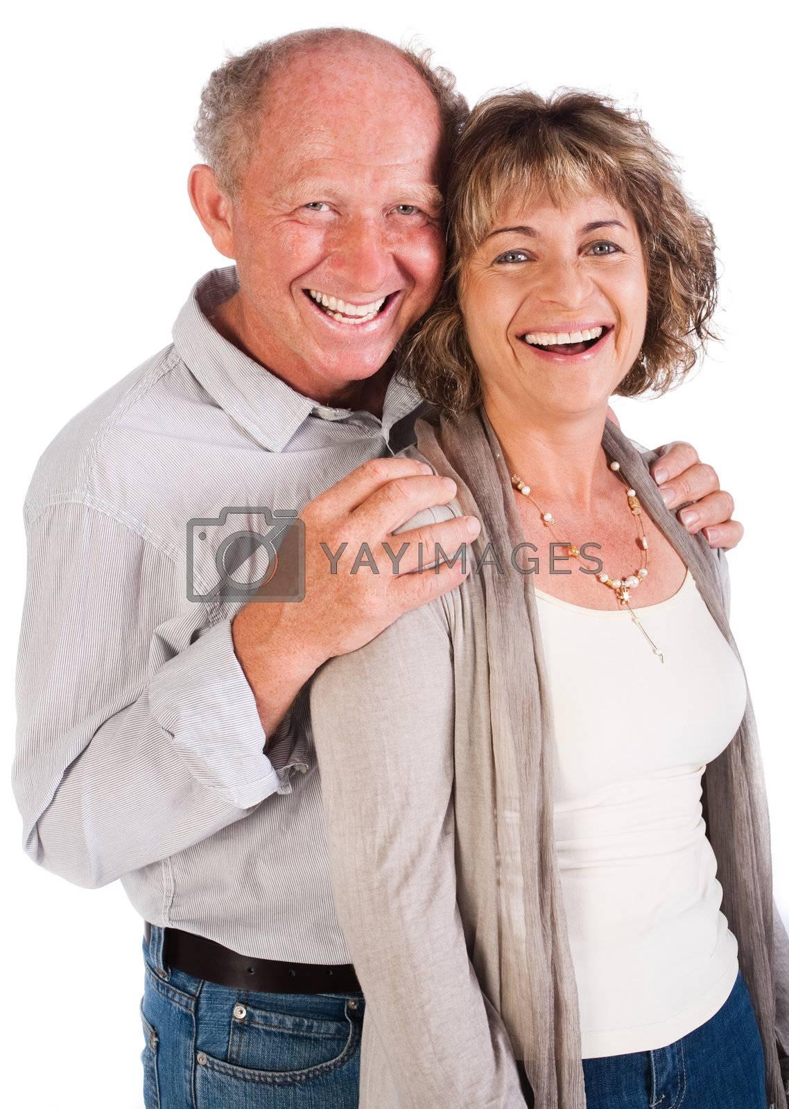 Senior couple posing in studio and smailing at camera.