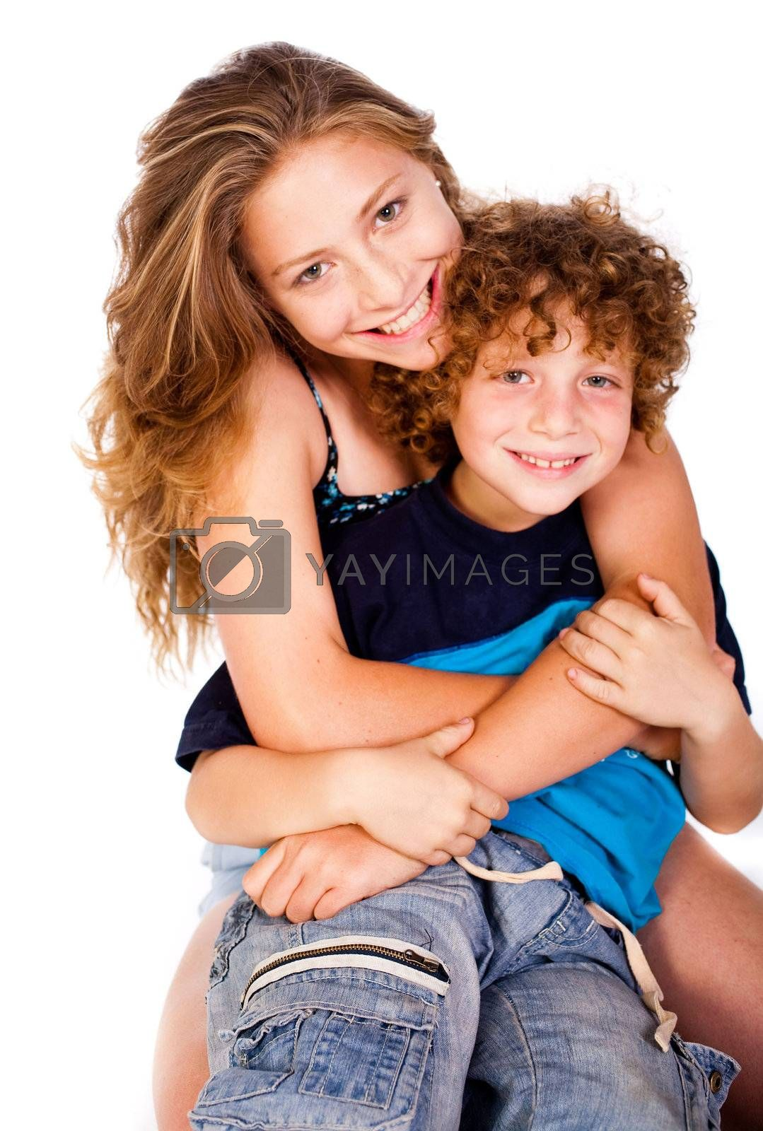 Mother hugging her lovable young kid and smiling at camera.