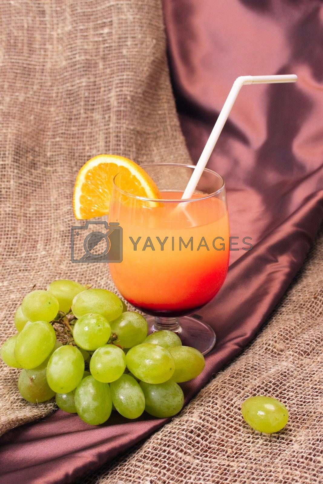 a picture of an orange cocktail with a branch of grape