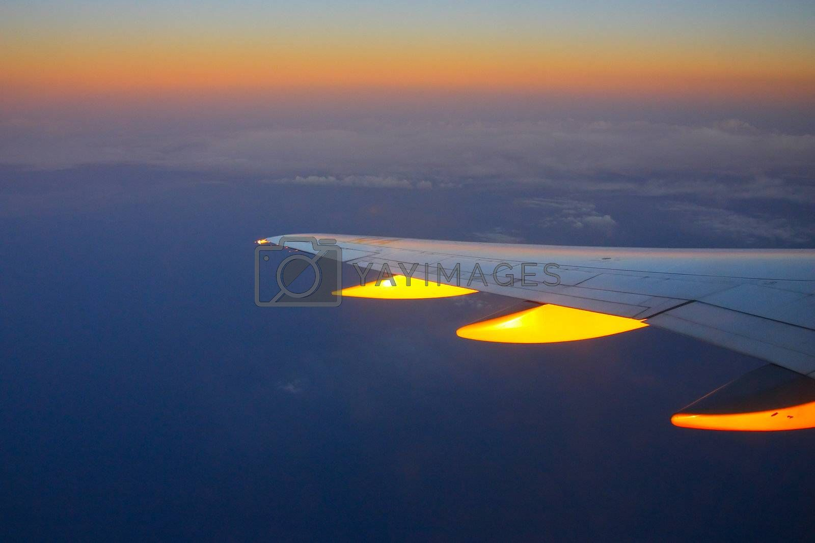 Wing of the plane on a background of gold clouds and sunset