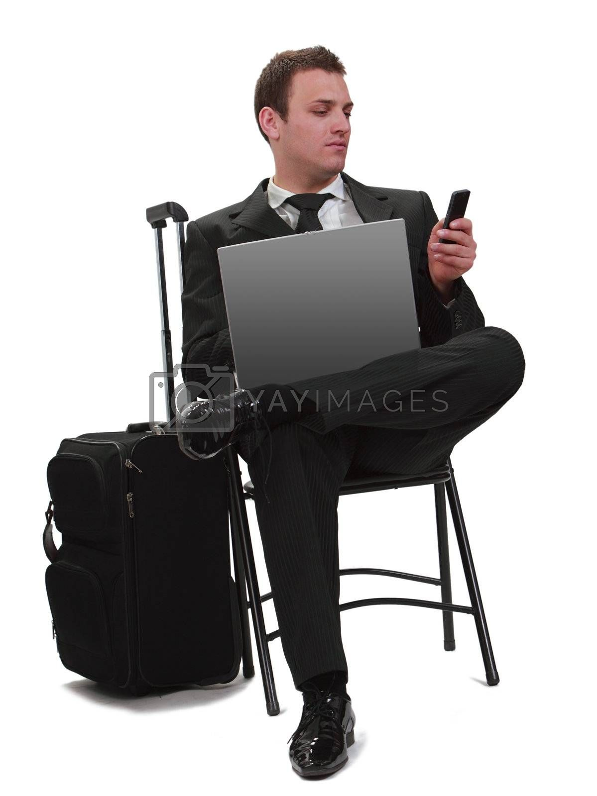 Young businessman reading a phone message while she is sitting with his laptop next to her suitcase,isolated against a white background.