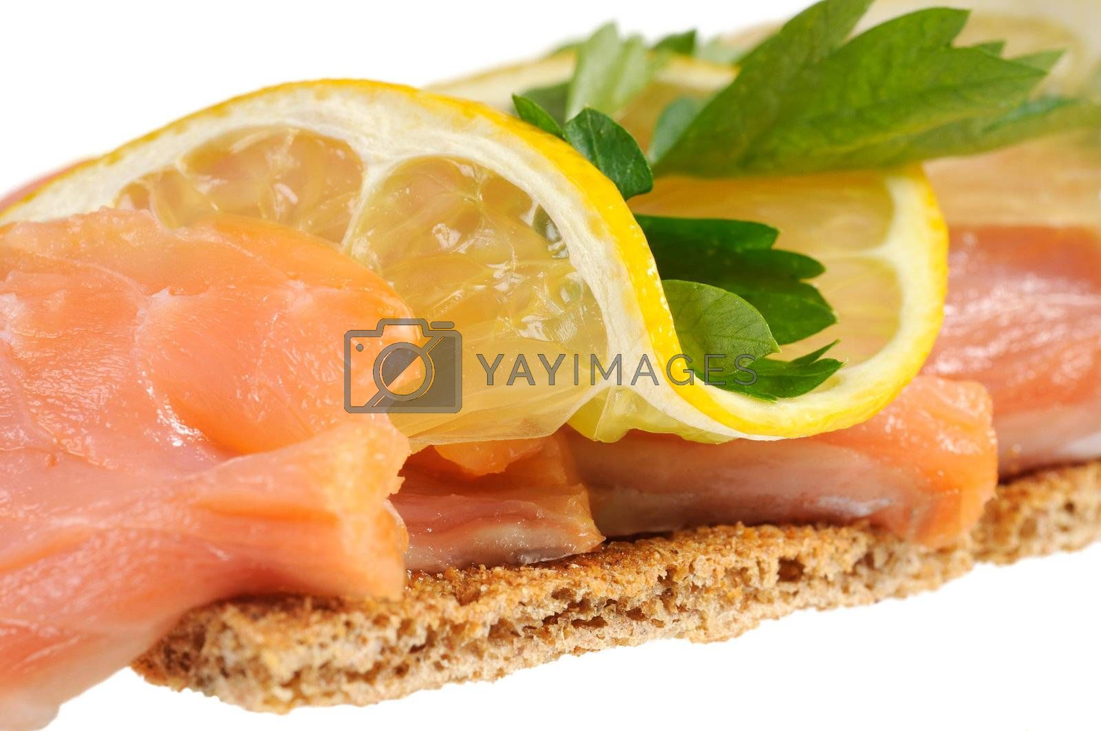 Sandwich snack - salmon with lemon on rye bread. Isolated on white.
