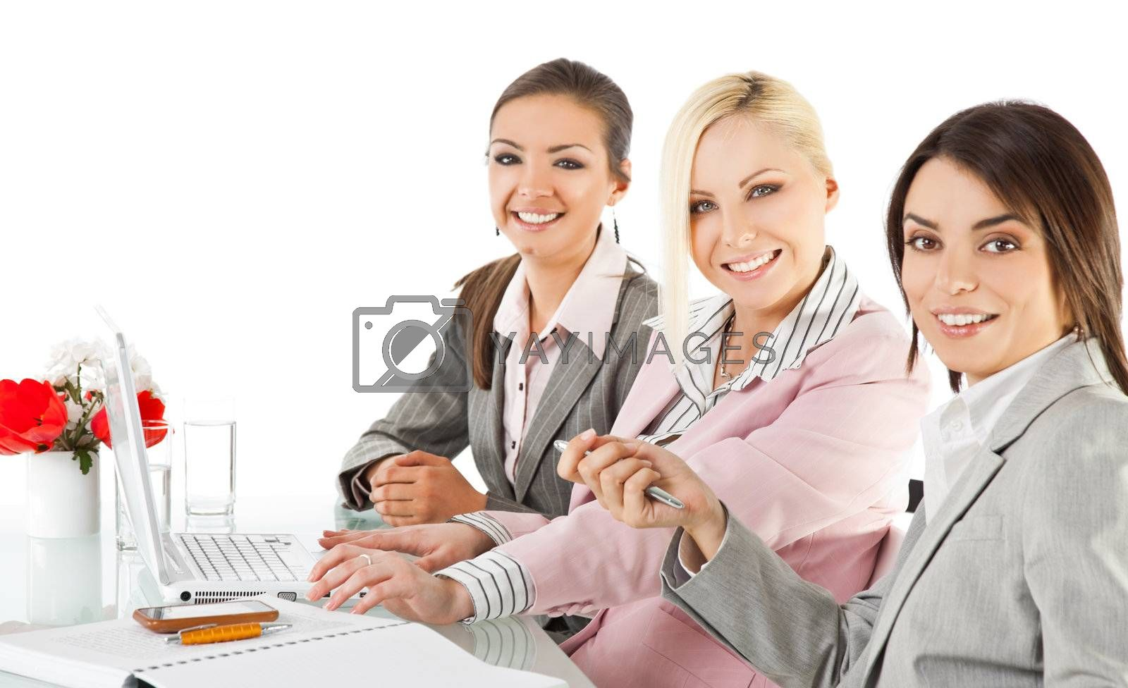 Group of three happy businesswomen working behind desk with laptop, looking at camera