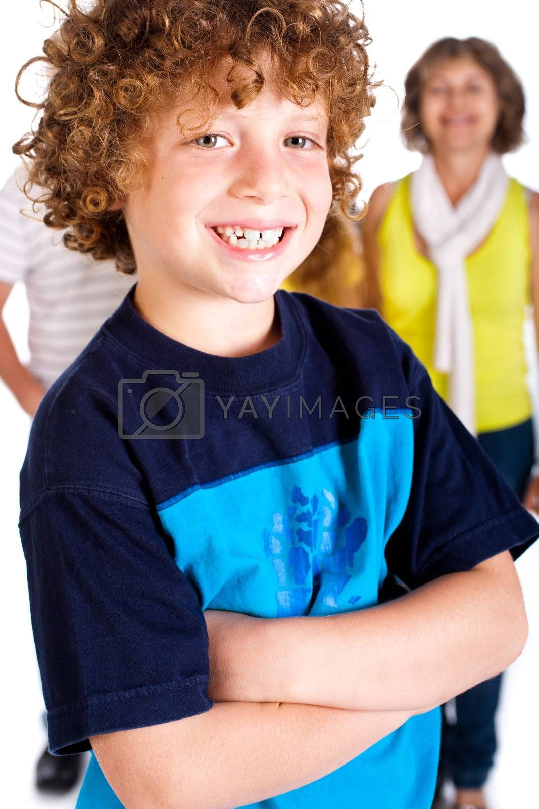 Young cute boy in focus with family in the background, isolated over white.