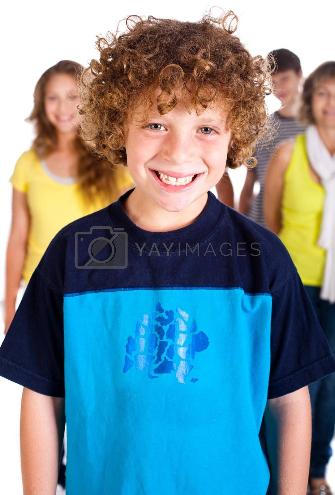 Smiling kid in focus with family posing in the background, isolated on white.