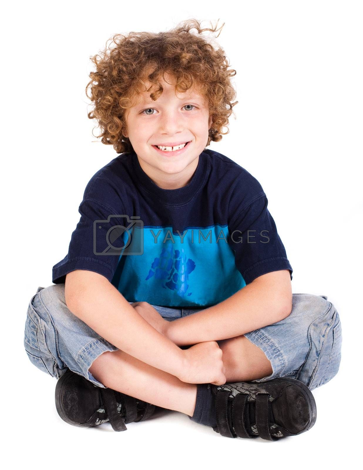 Cheerful kid relaxing on floor isoalted agianst on white.