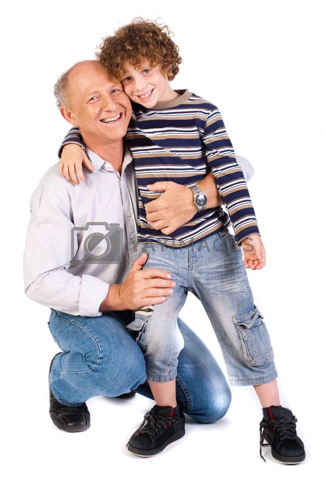 Grandfather embracing his grandson, indoors against white background..