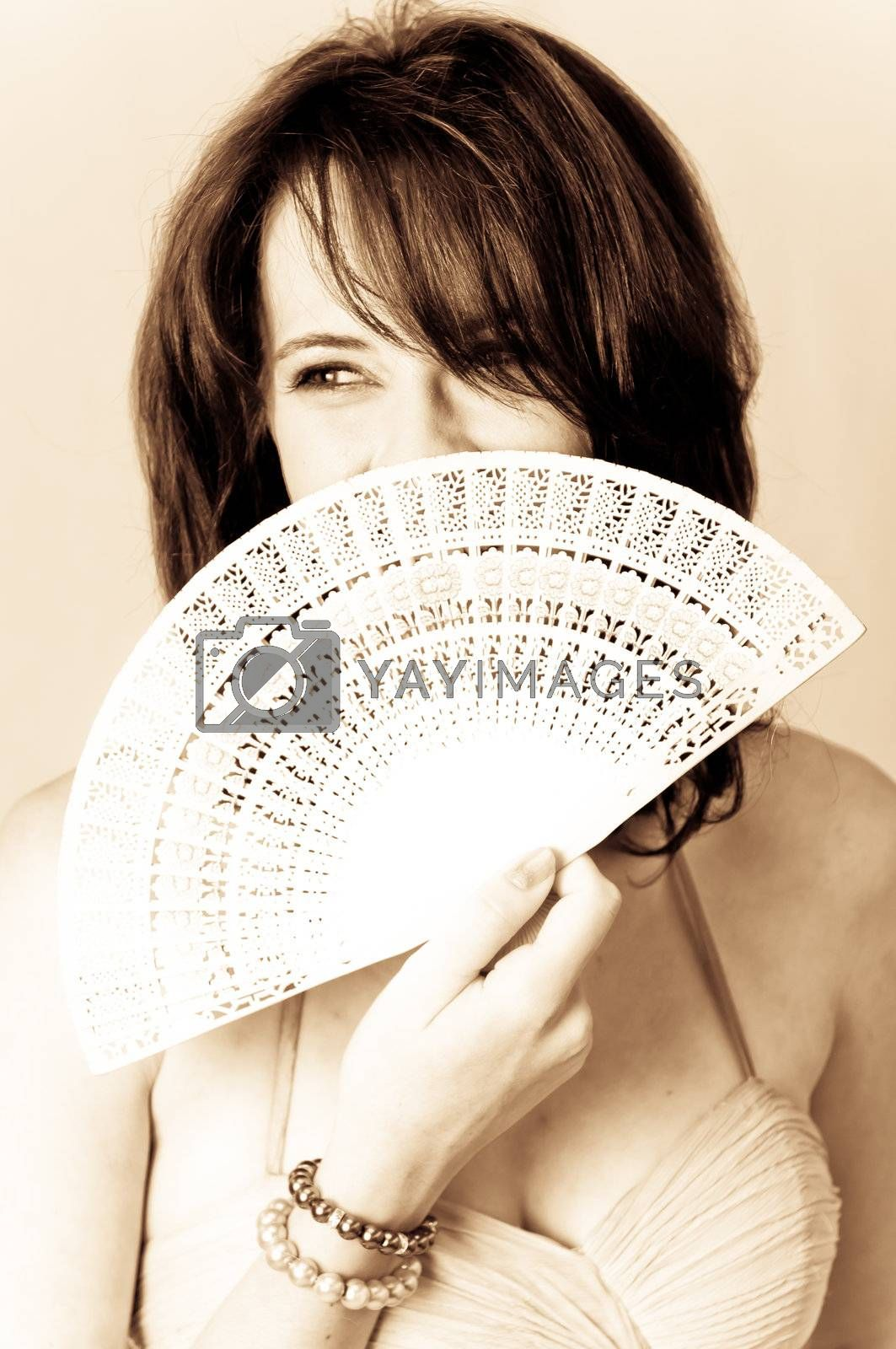 Sepia image of beautiful young brunette sexy model holding a white with Chinese hand fan in front of her face