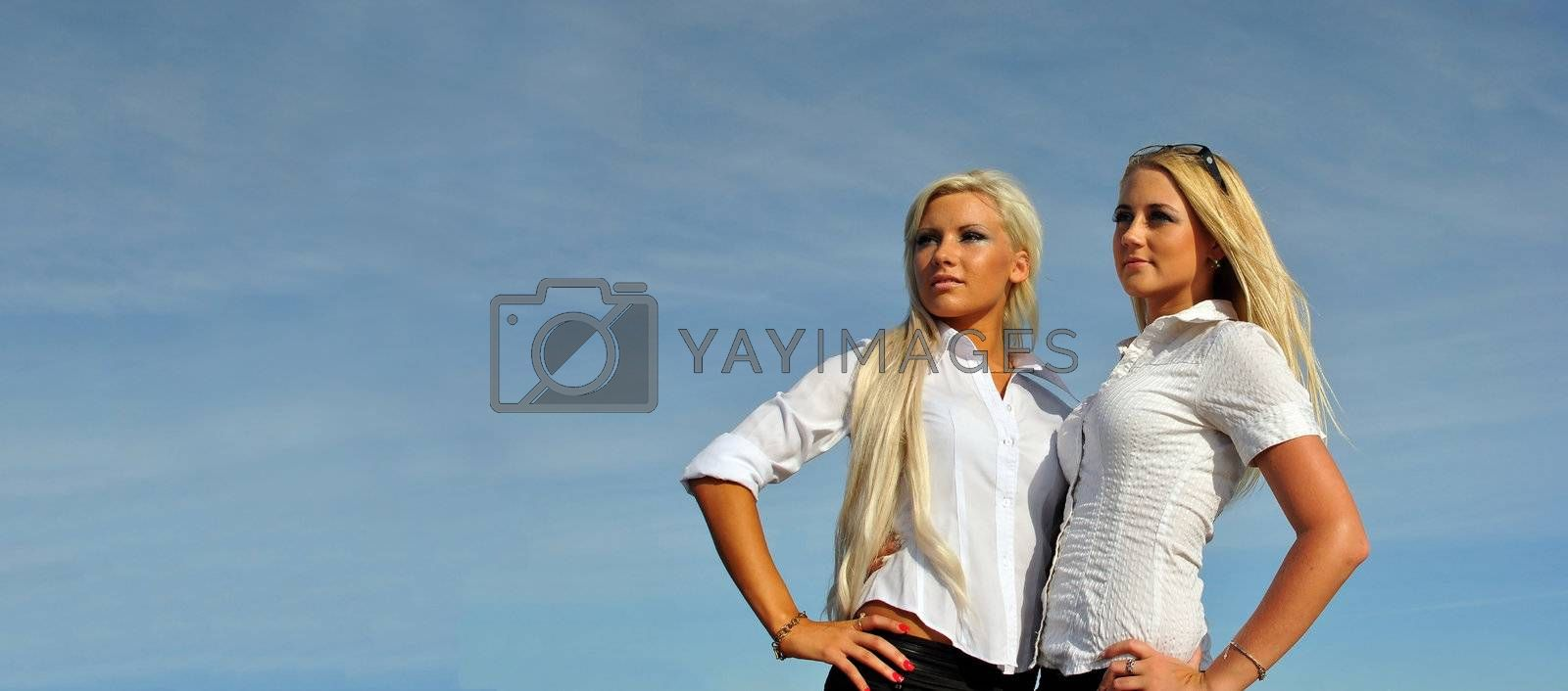 Two blonde girls on sky background. Perfect for placing your own advertisements on