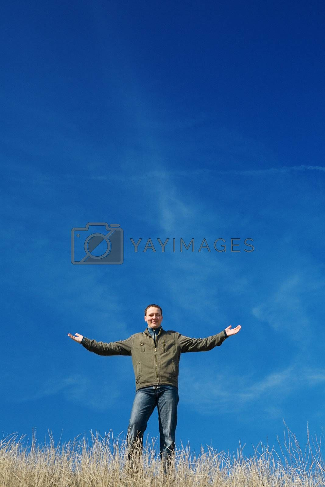 successful and happy man stay on a background of the blue sky