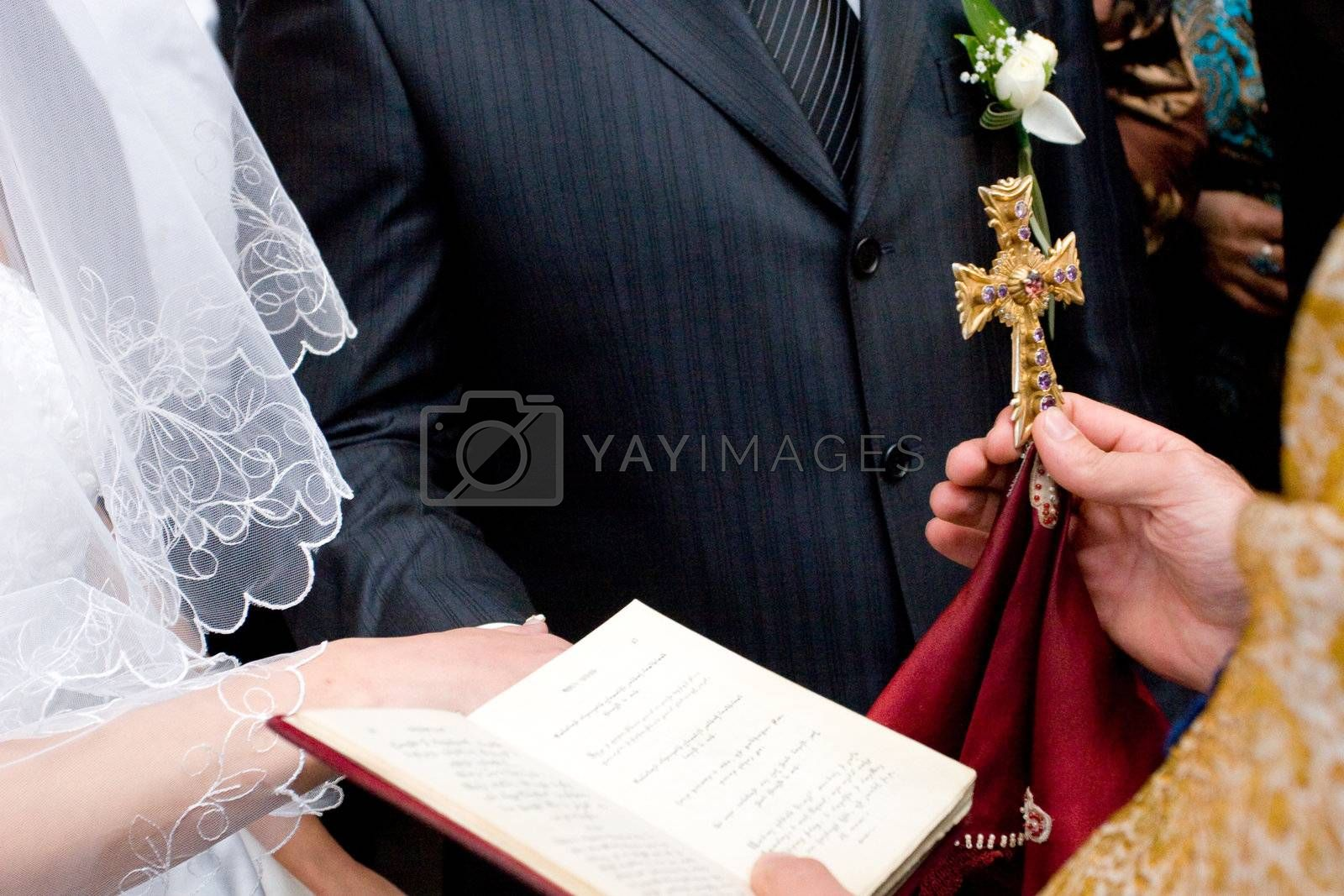 cross and Bible in the hands of the priest