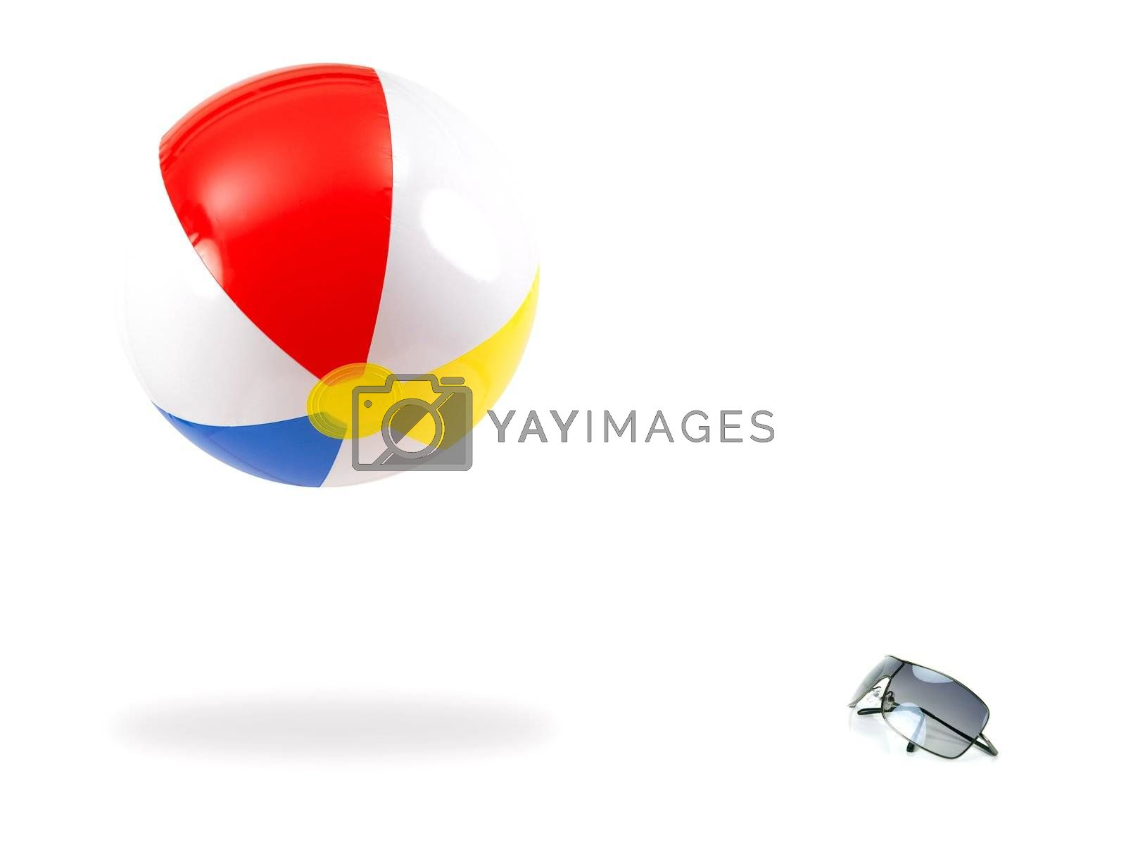 Sunglasses and a beach ball isolated against a white background