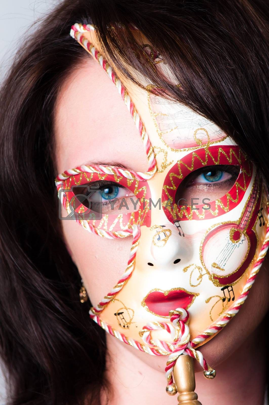 Beautiful young brunette haired, blue eyed sexy model dressed in gold with colourful red and gold venetian carnival face mask